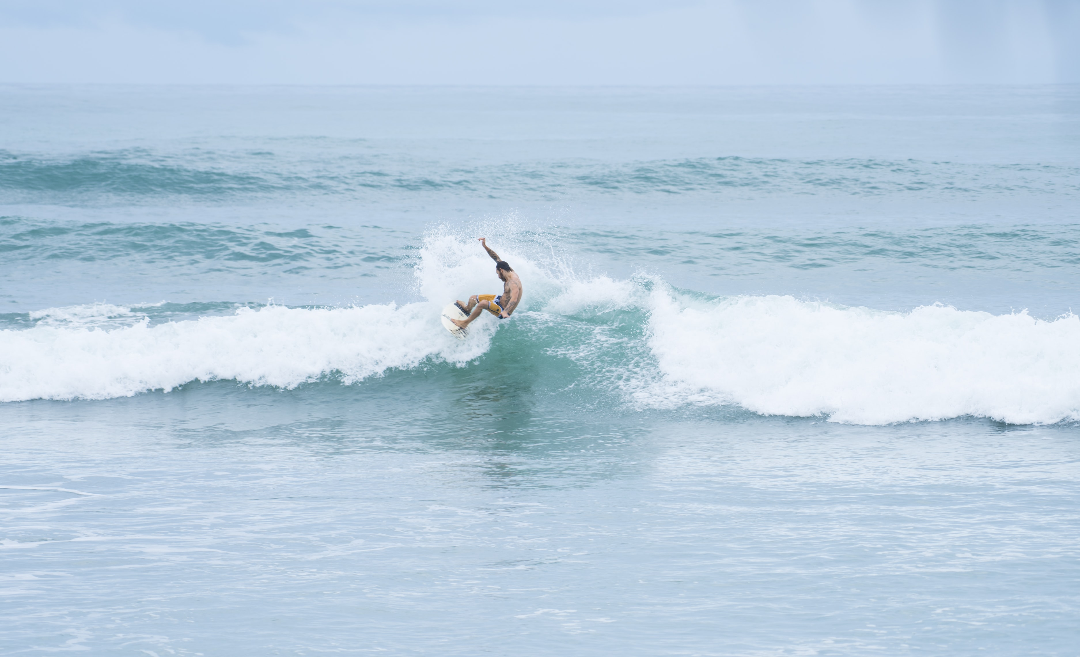 man riding a surfboard facing the waves on the ocean