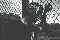 grayscale photo of person holding cyclone fence