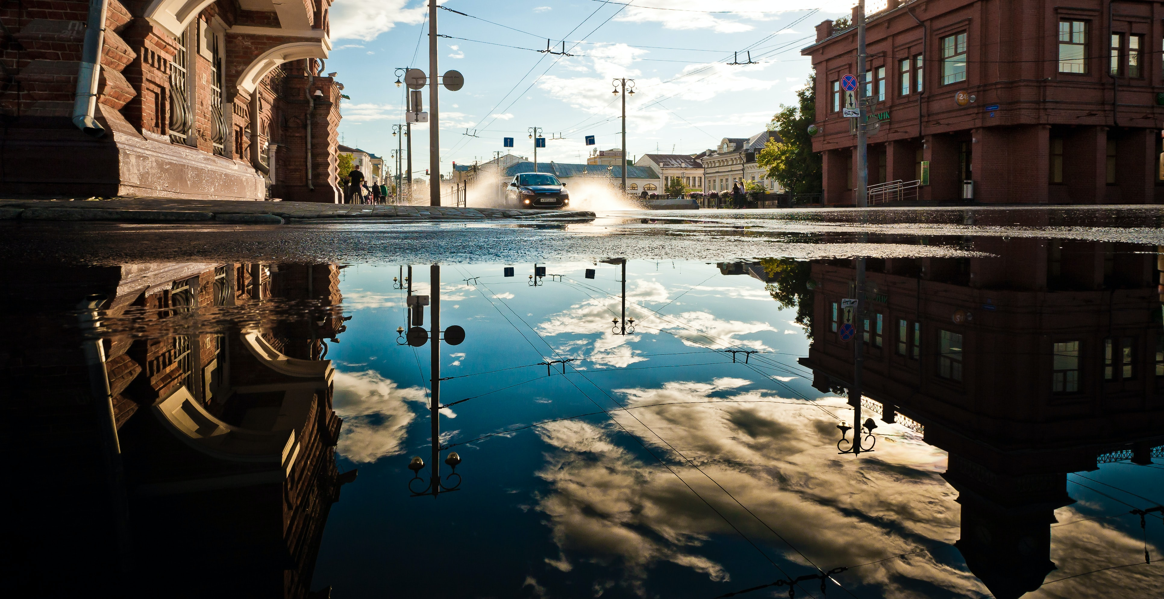 Black car driving through puddle reflecting the sky and buildings on a street in Vladimir