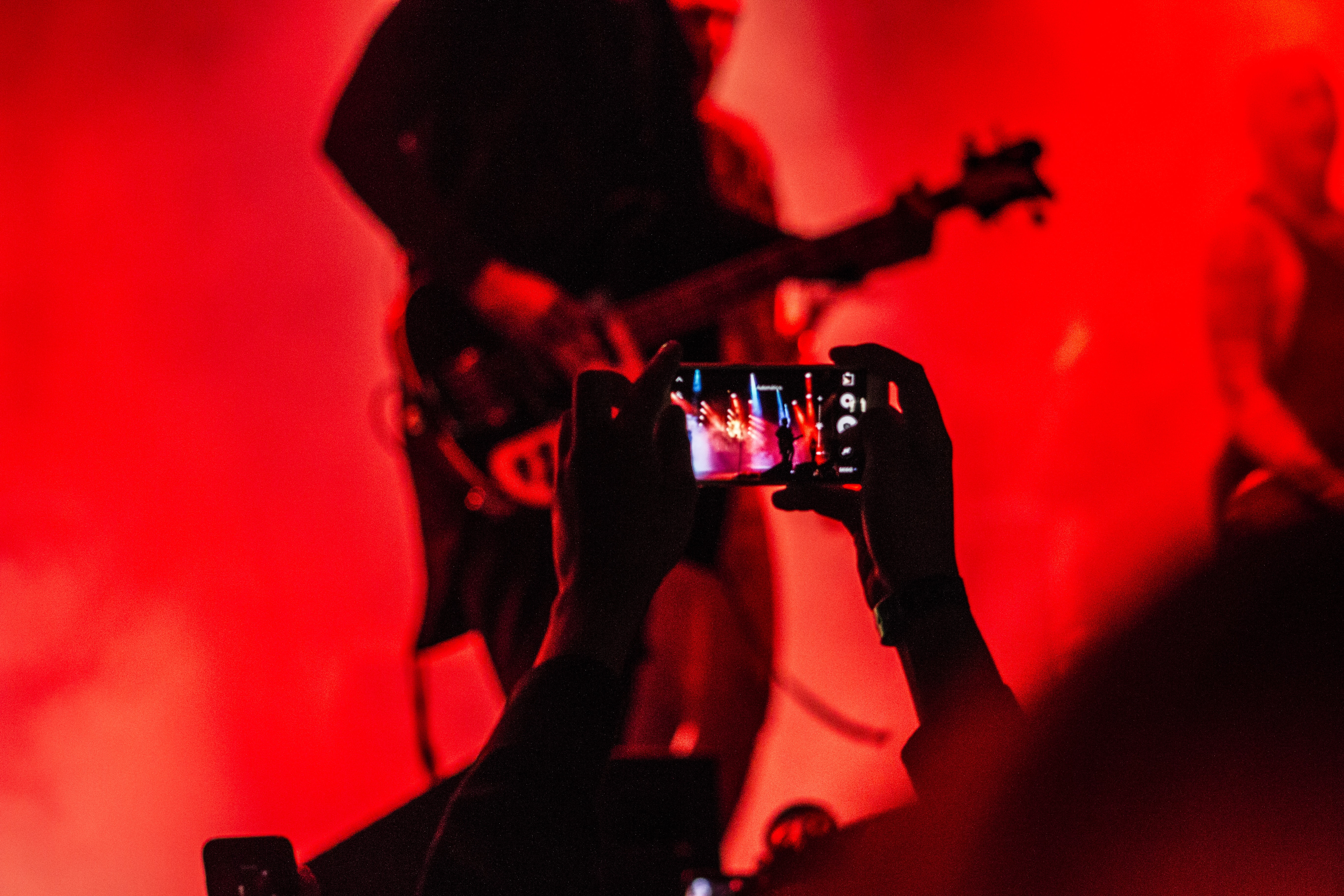 A guitarist performs on stage in red light while an audience member records a concert on their phone