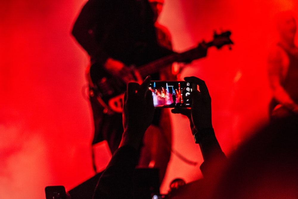 person holding smartphone in front of a person playing guitar on stage