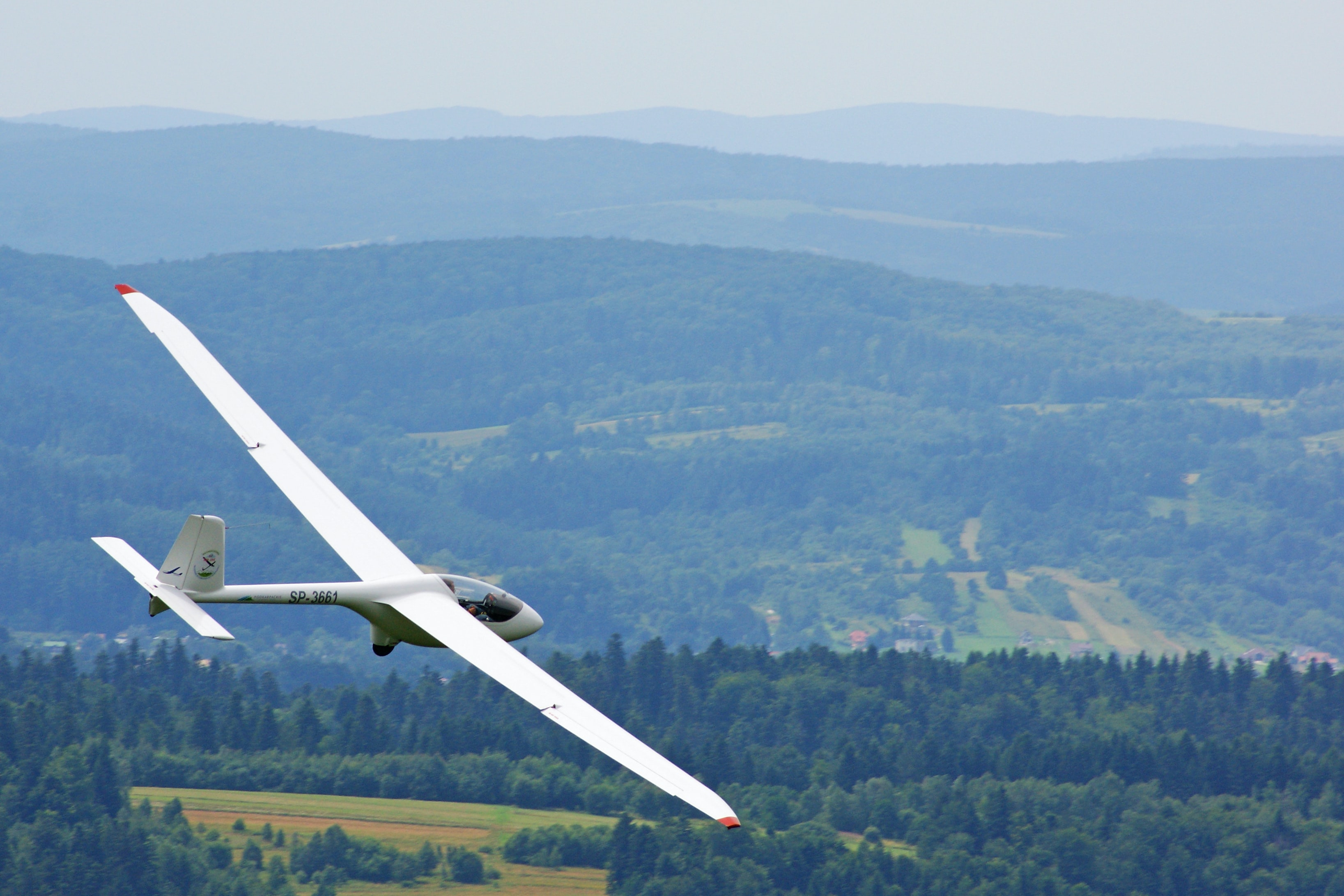 A white glider in flight over forested hills