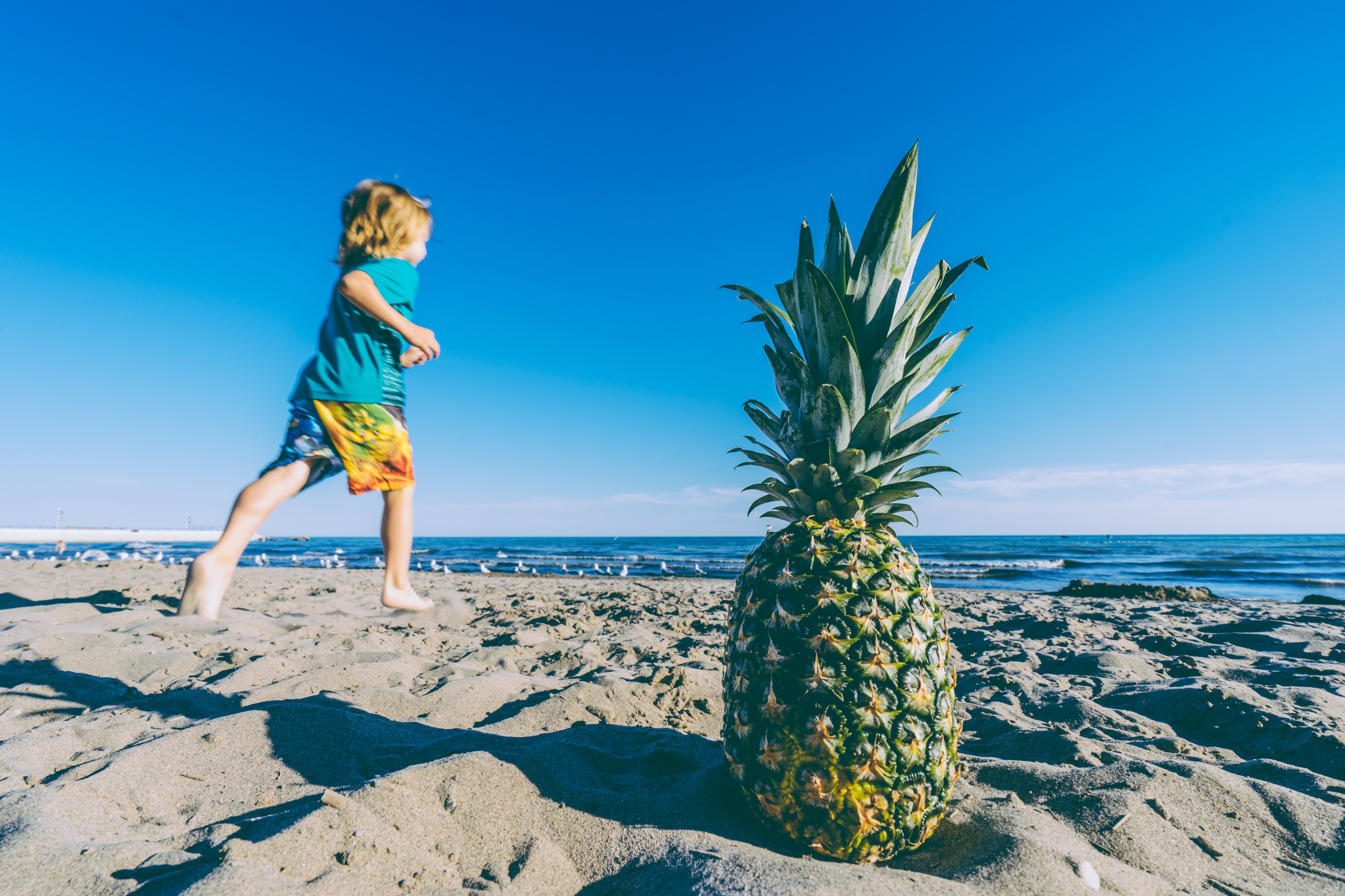 selective focus photo of green and yellow pineapple near running kid wearing blue T-shirt photo taken during daytime