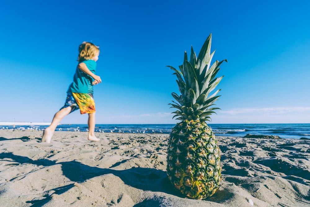 selective focus photo of green and yellow pineapple near running kid wearing blue T-shirt photo taken during daytime