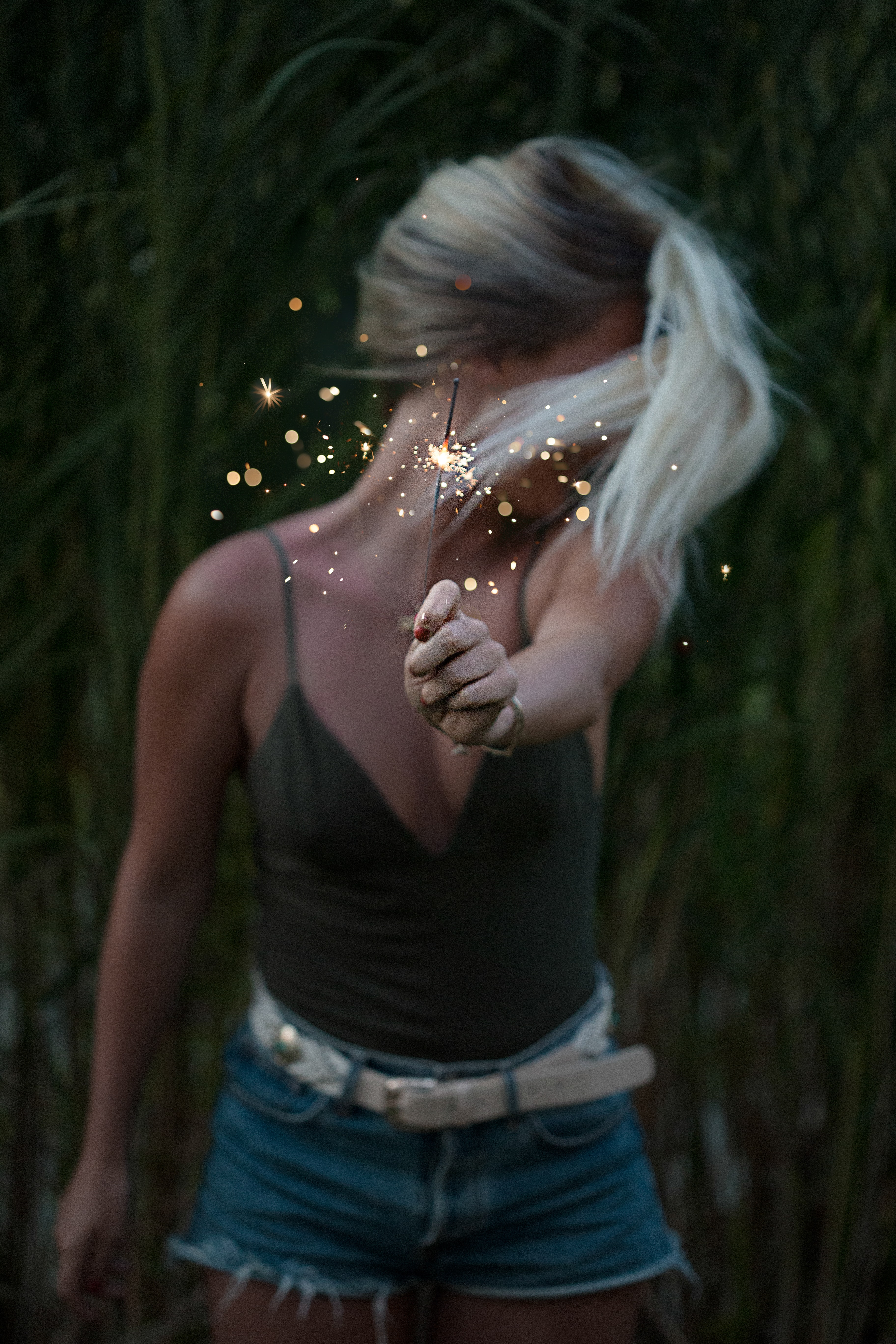 A blonde woman holding a lit sparkler and looking away