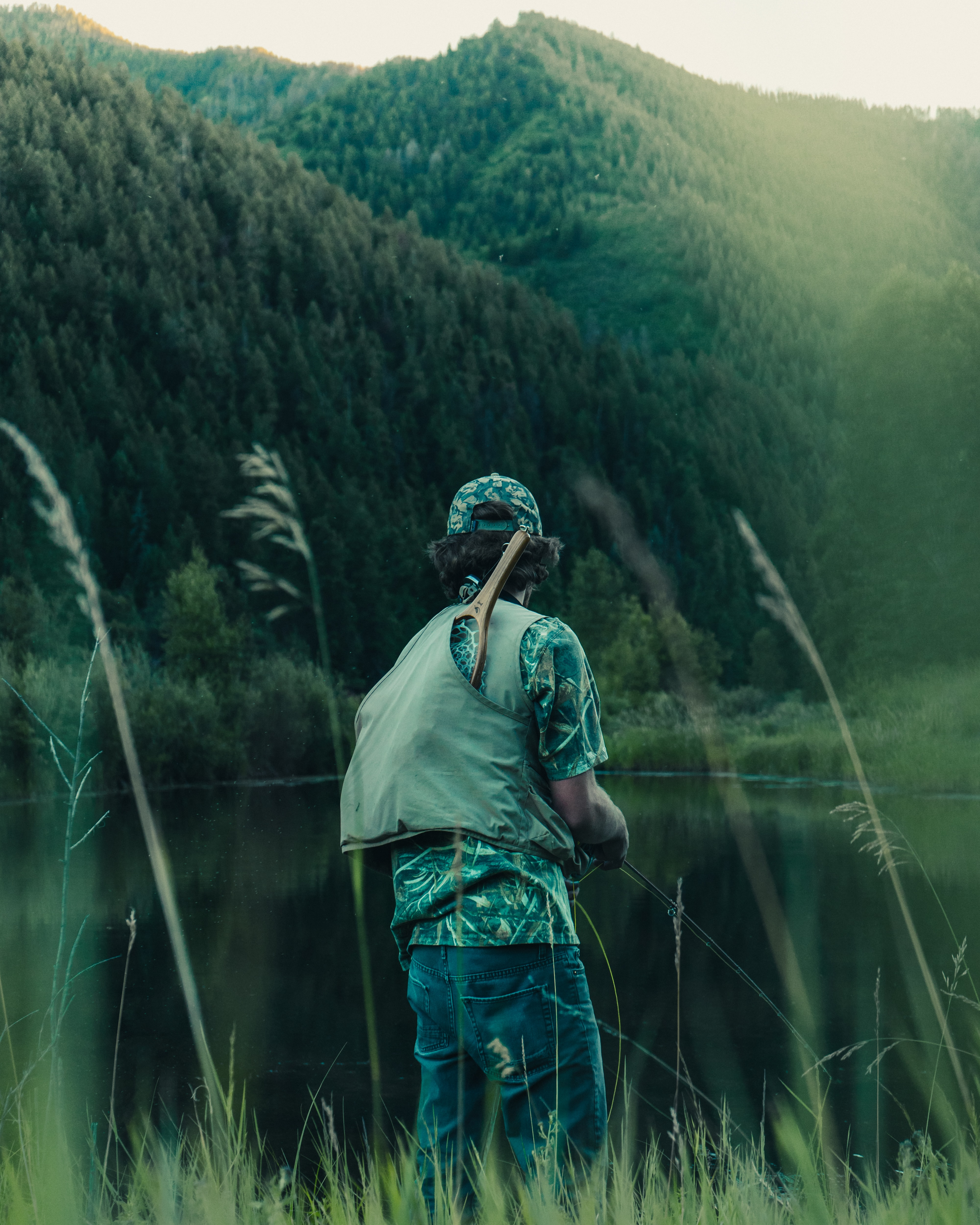 A man with a fishing net on his back over a mountain lake