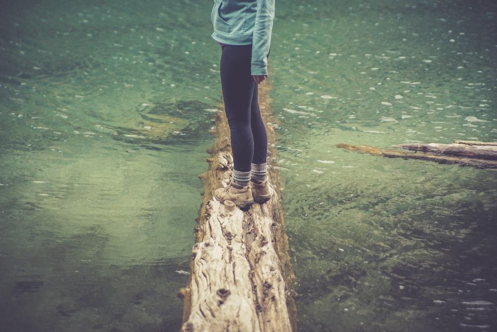 woman standing on log