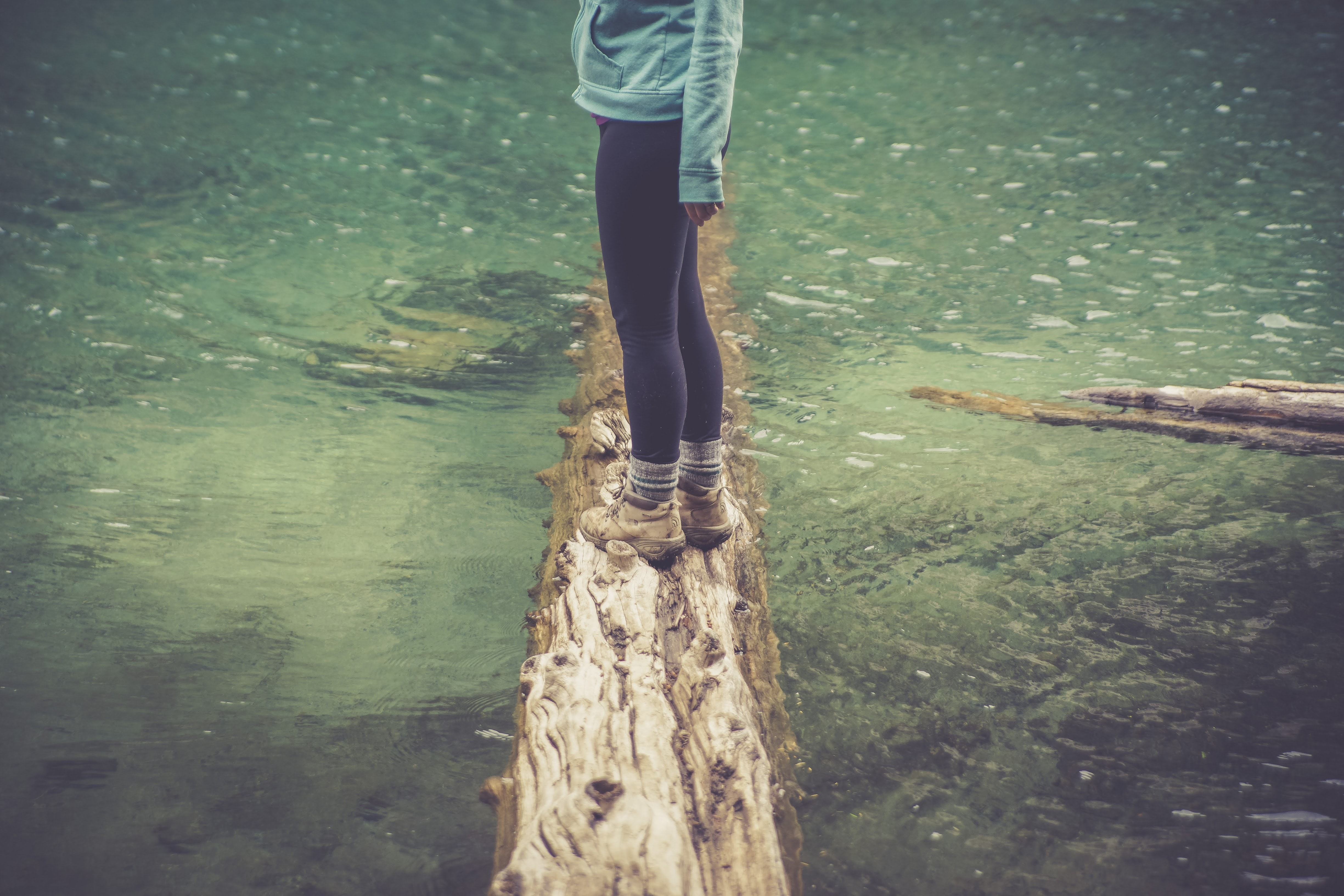 A woman standing on a log submerged in a lake