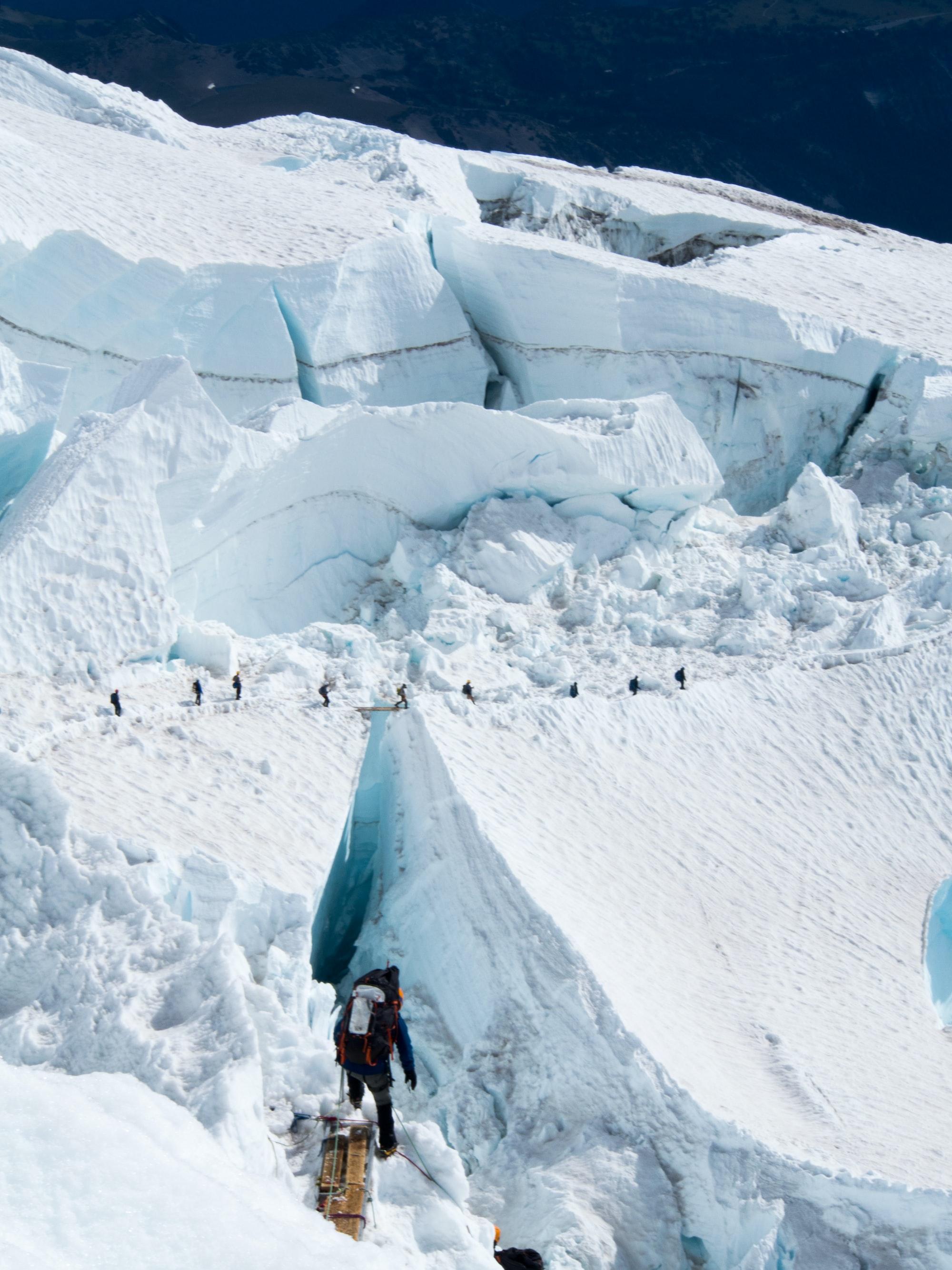 Ein Bergsteiger auf dem Mount Everest beobachtet eine Gruppe Bergsteiger, die eine Schlucht überqueren.