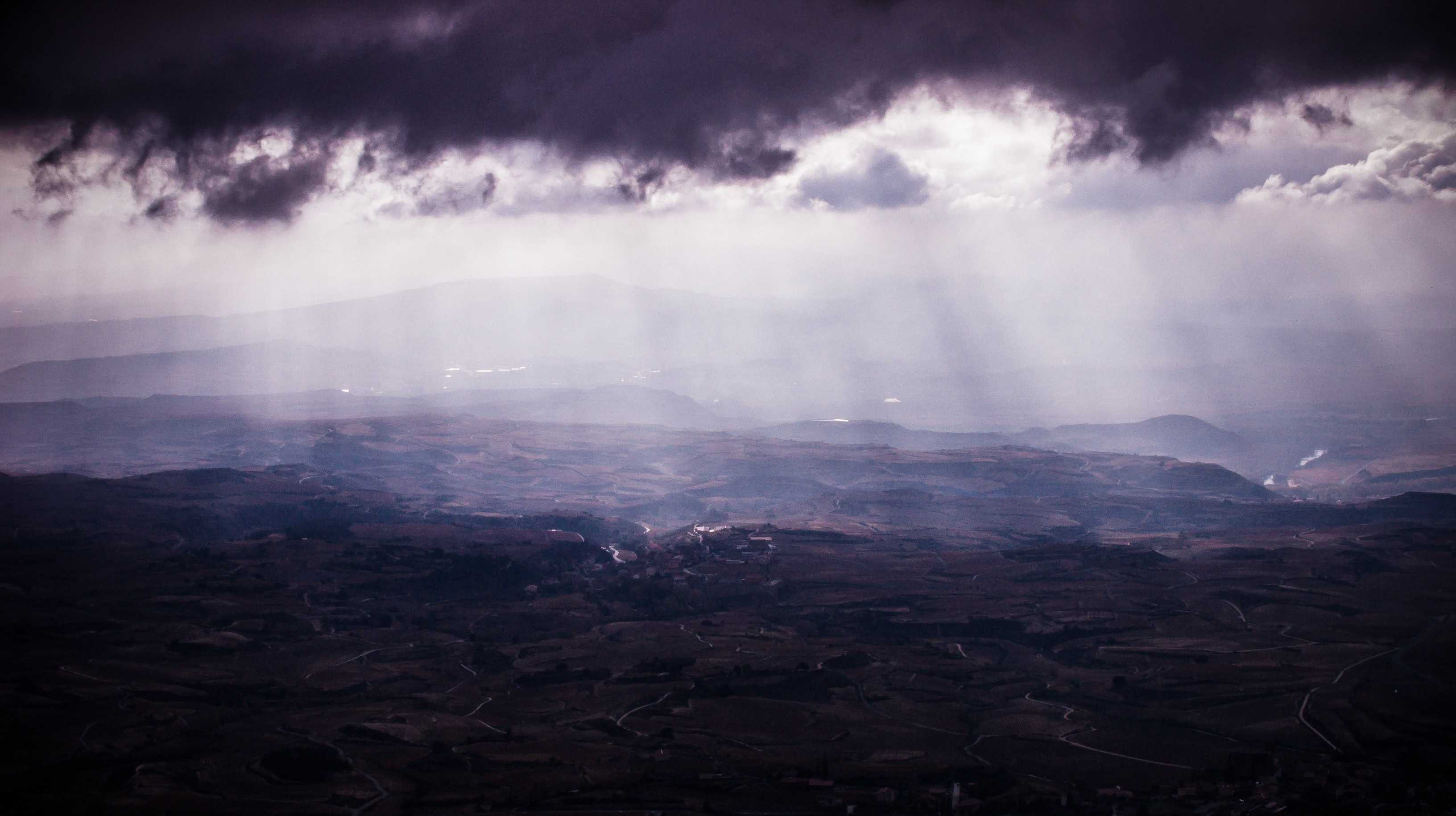 A vast rural landscape under faint light seeping in from the clouds