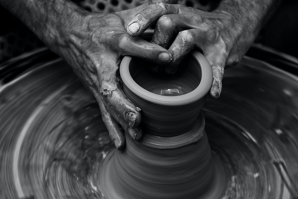 Messy hands sculpting on a pottery wheel in motion