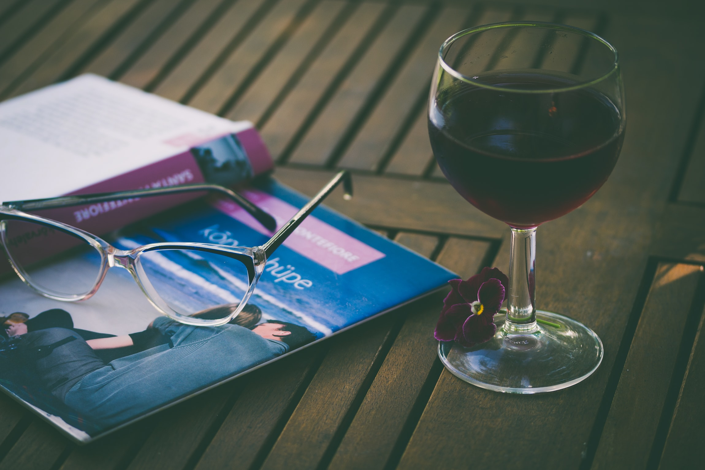 A glass of red wine on the table, along with a pair of eyeglasses and a book.