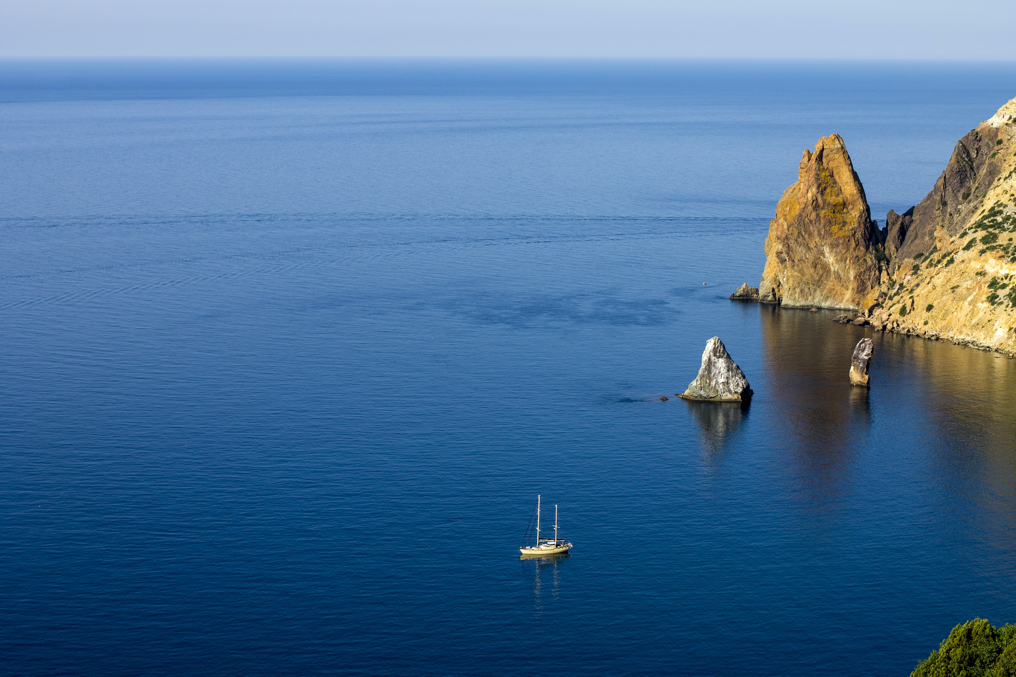 aerial photography of white ship on sea near rock formations under blue sky during daytime