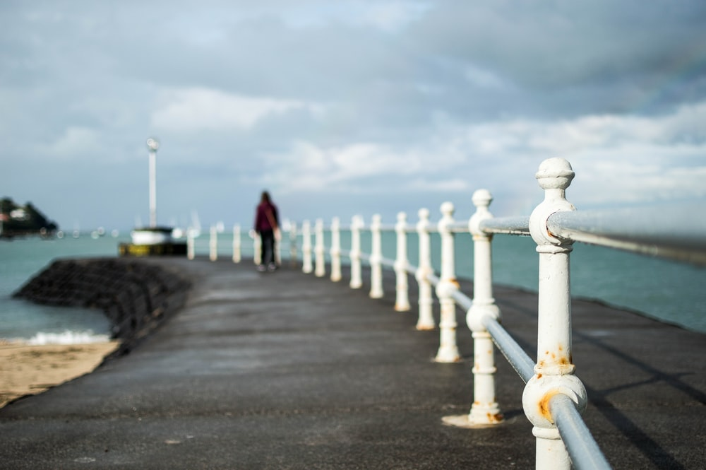 shallow focus photography of man near shore during daytime
