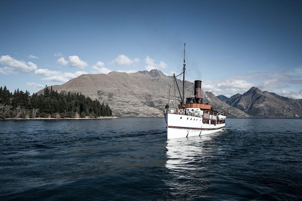 white ship near island of mountain during daytime