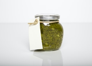 clear glass jar with green kush inside