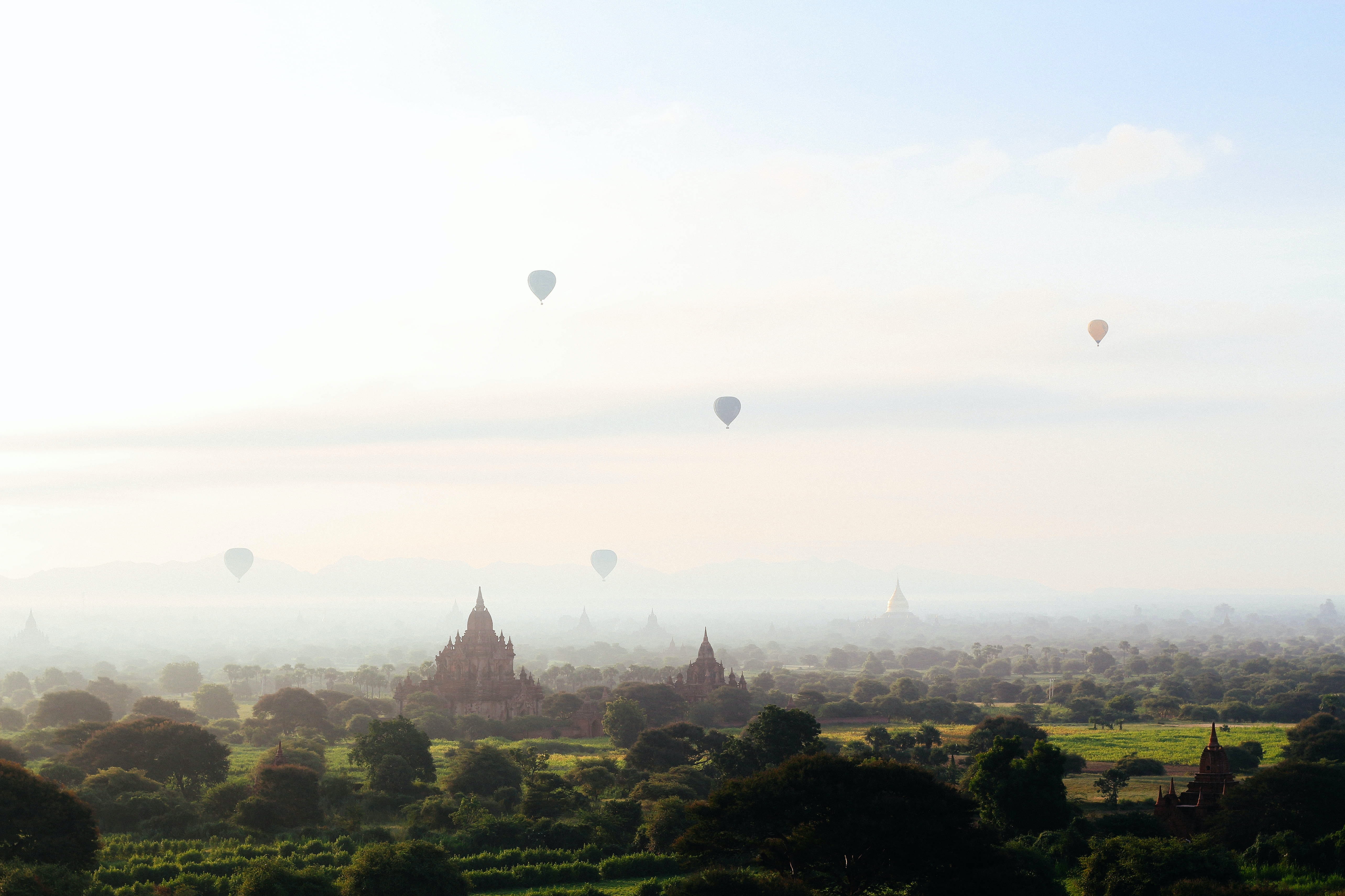 A landscape view of temples with hot air balloons going into the sky in old began.