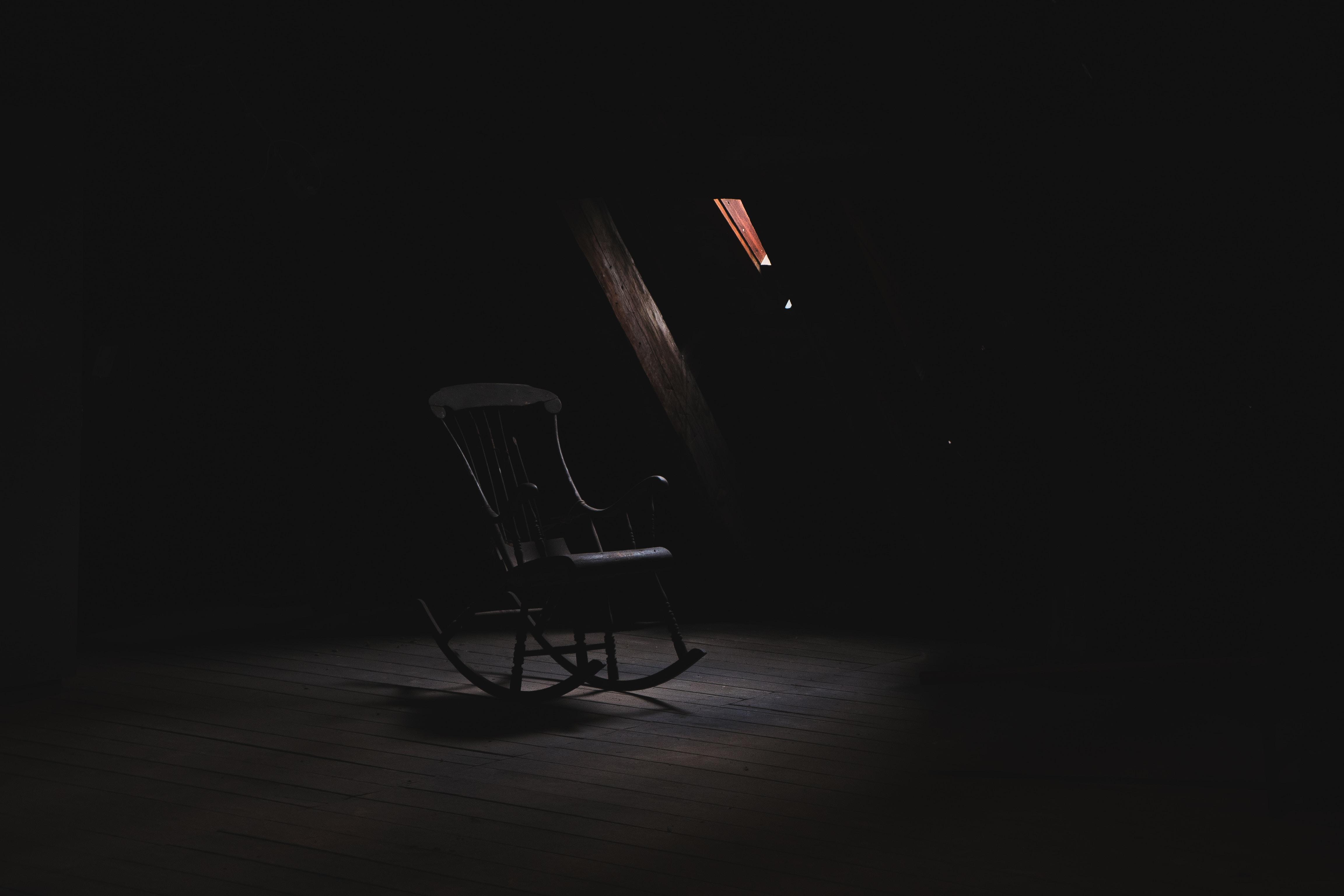 Single black rocking chair in middle of dark room in Copenhagen
