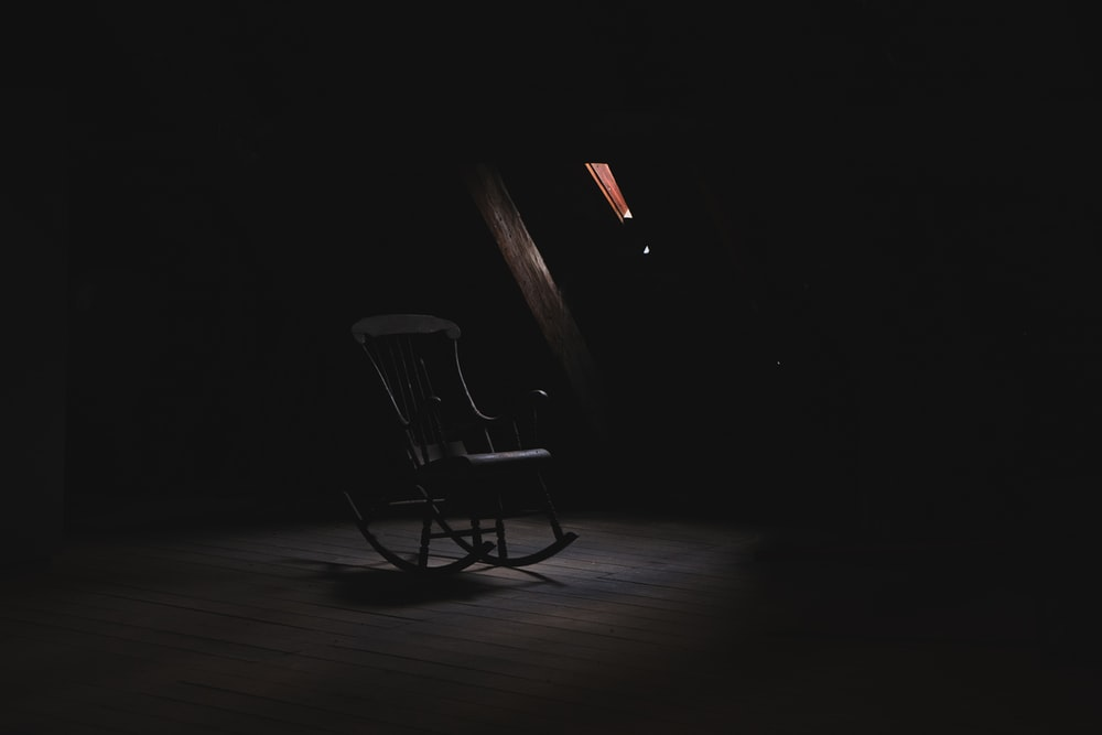 brown wooden rocking chair inside dark room