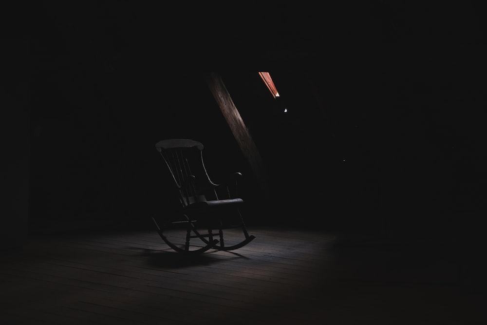 brown wooden rocking chair inside dark room