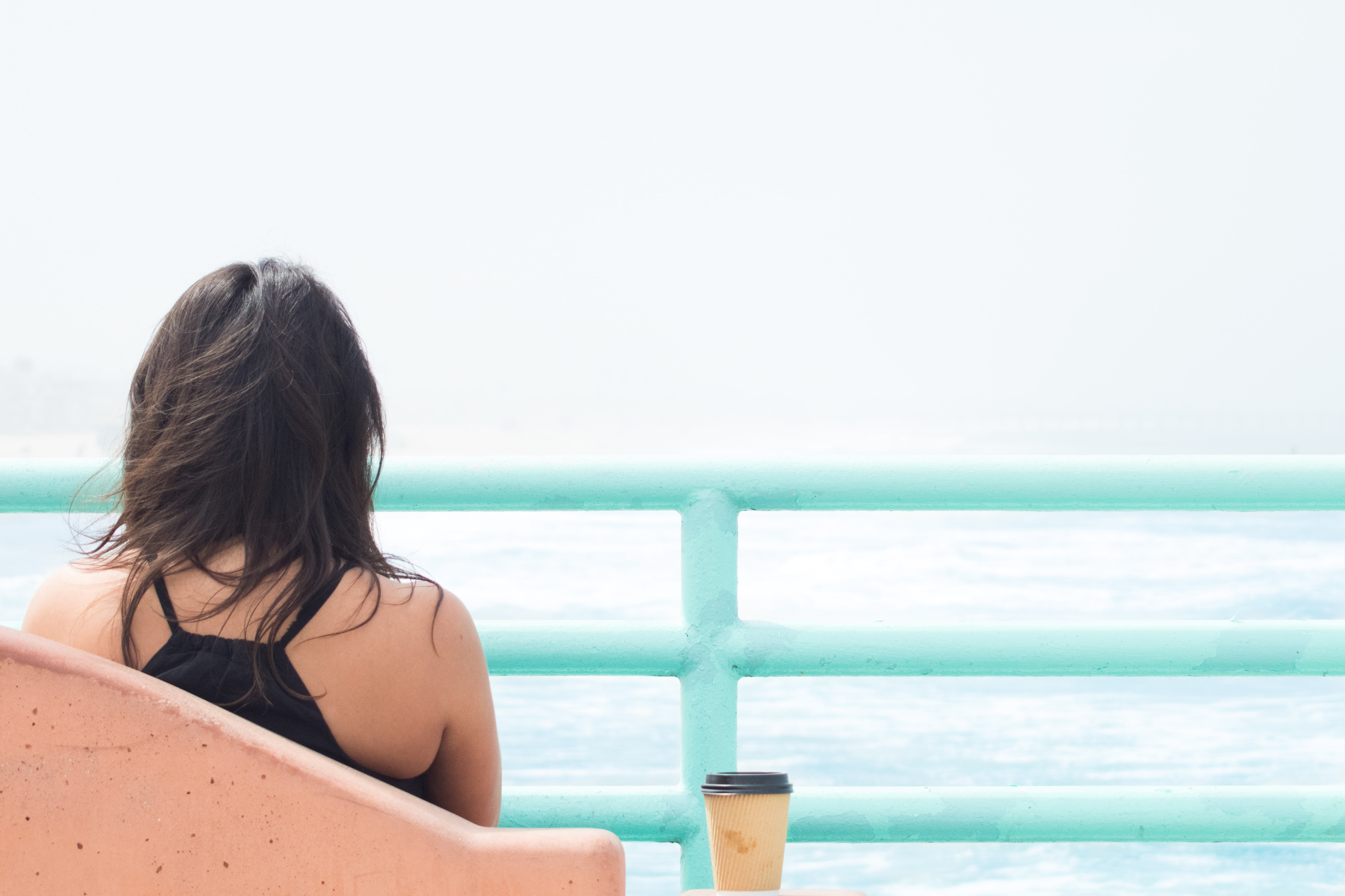 Woman sitting alone with cup of coffee behind light blue railing at Manhattan Beach
