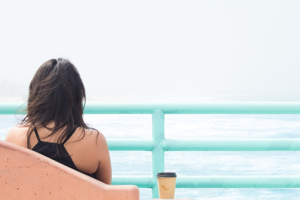 woman sitting on chair beside cup in front of body of water