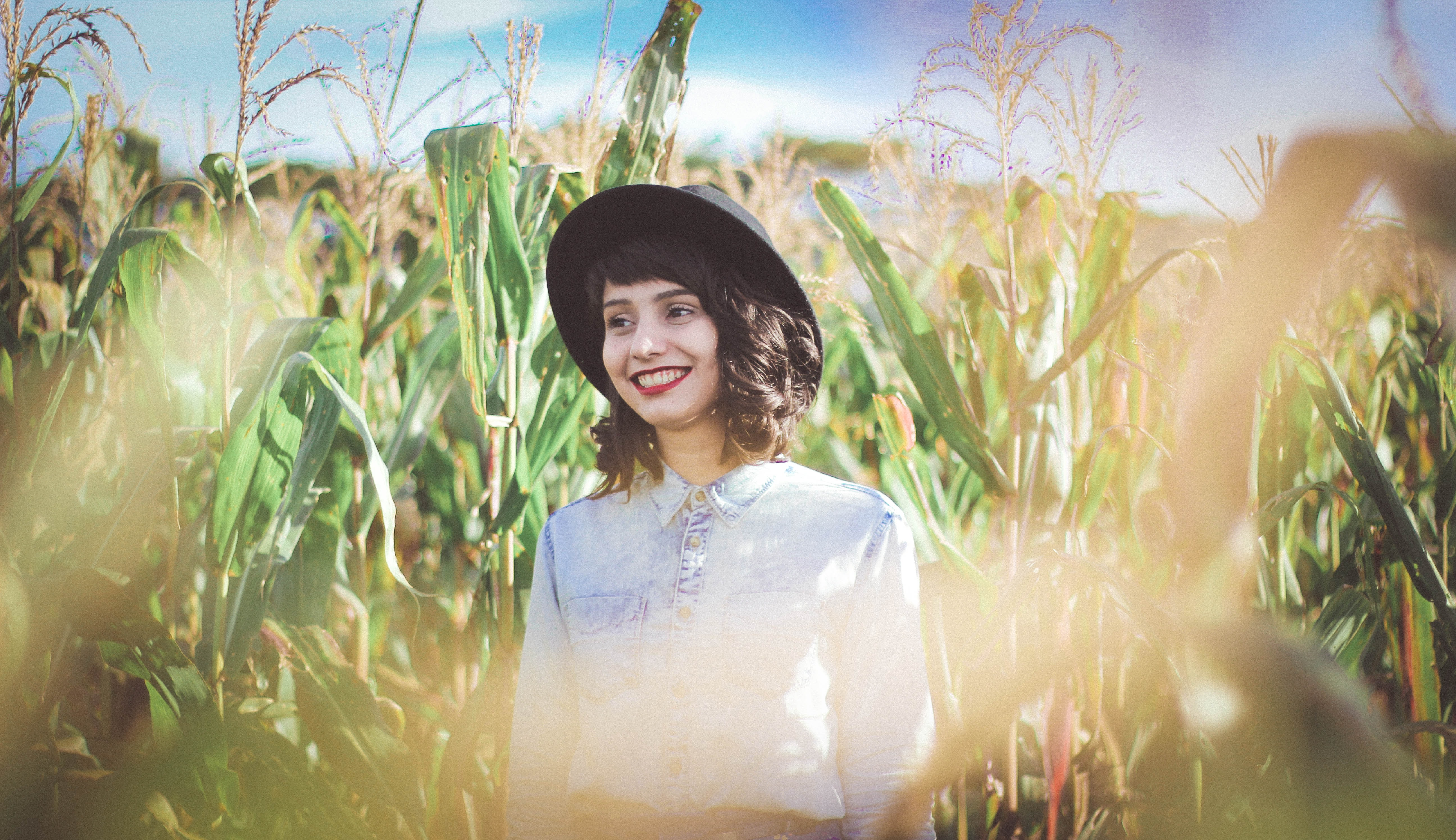 A woman wearing a hat and red lipstick standing in the middle of a cornfield