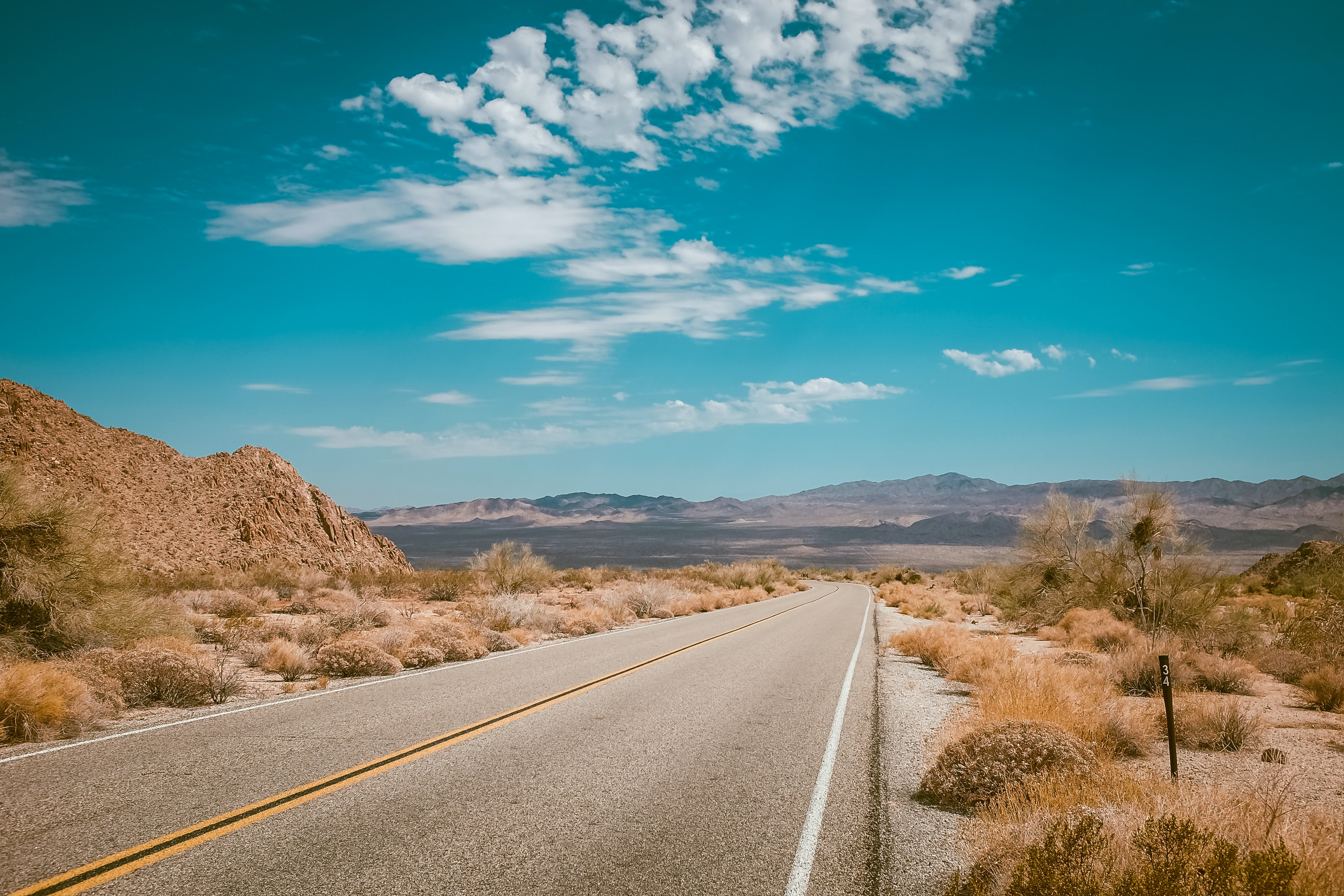 Empty highway across the desert with blue sky and mountains in the background