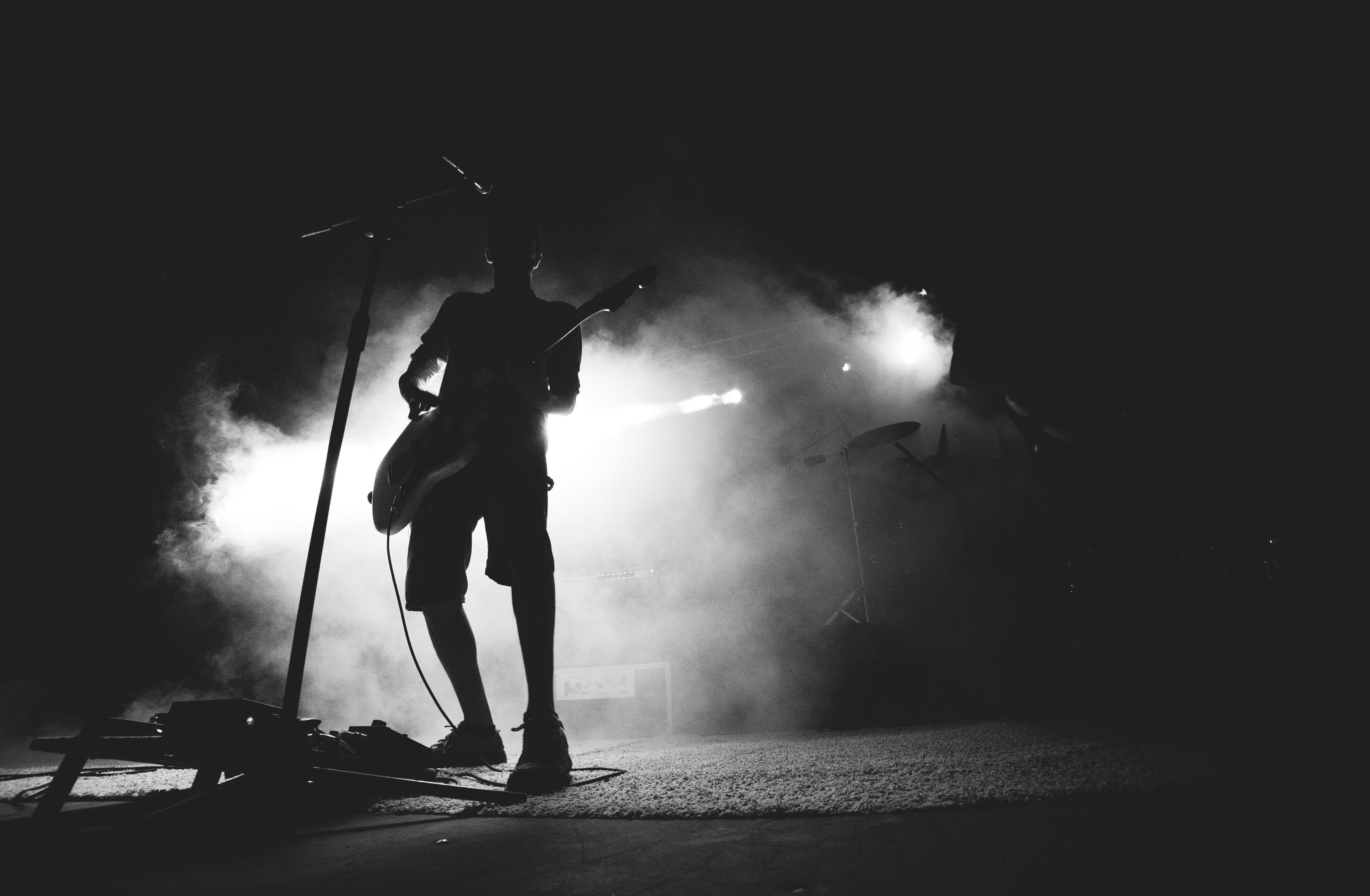 A black-and-white shot of a guitarist in thick smoke