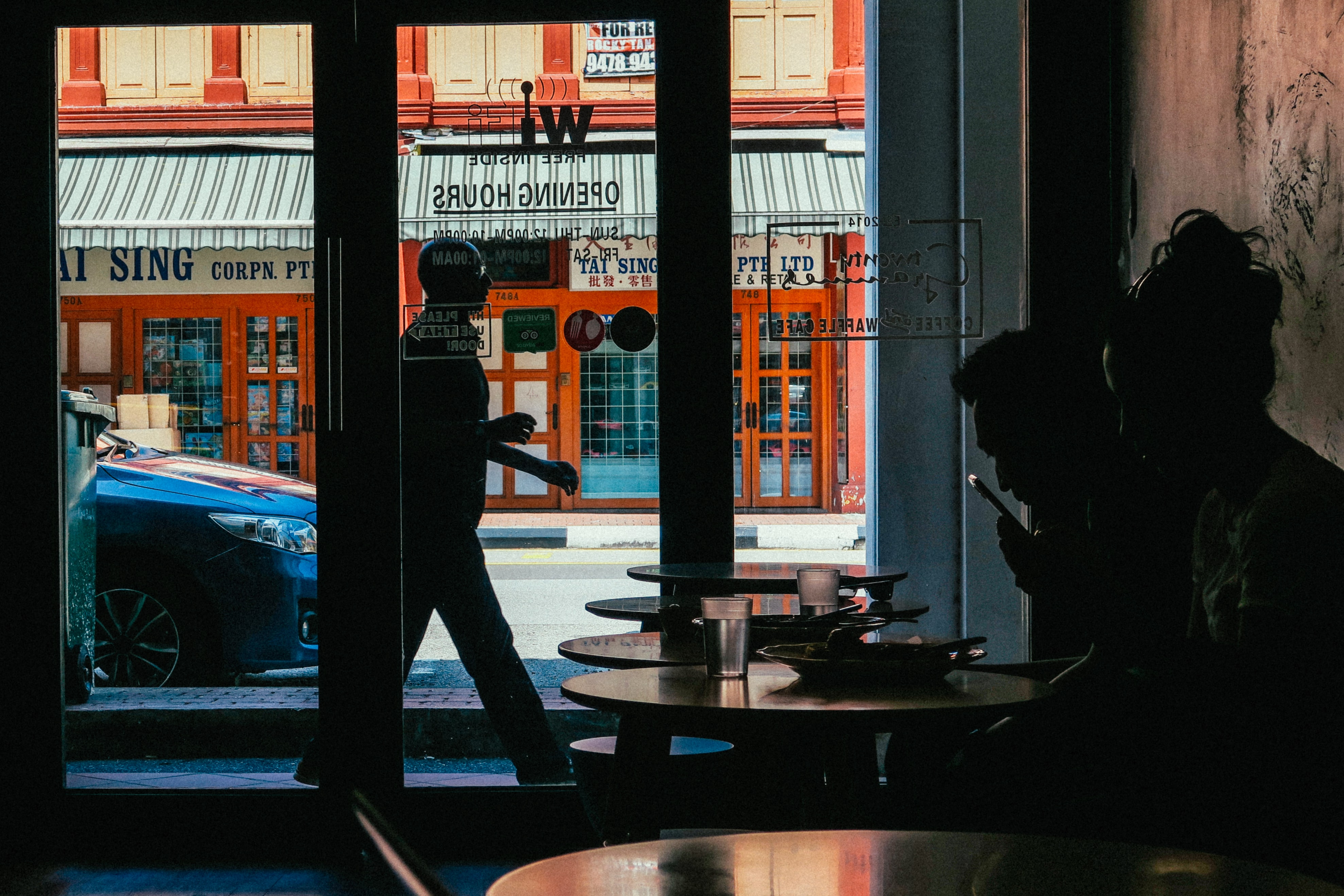 People in cafe with man walking past on sidewalk with sign on window