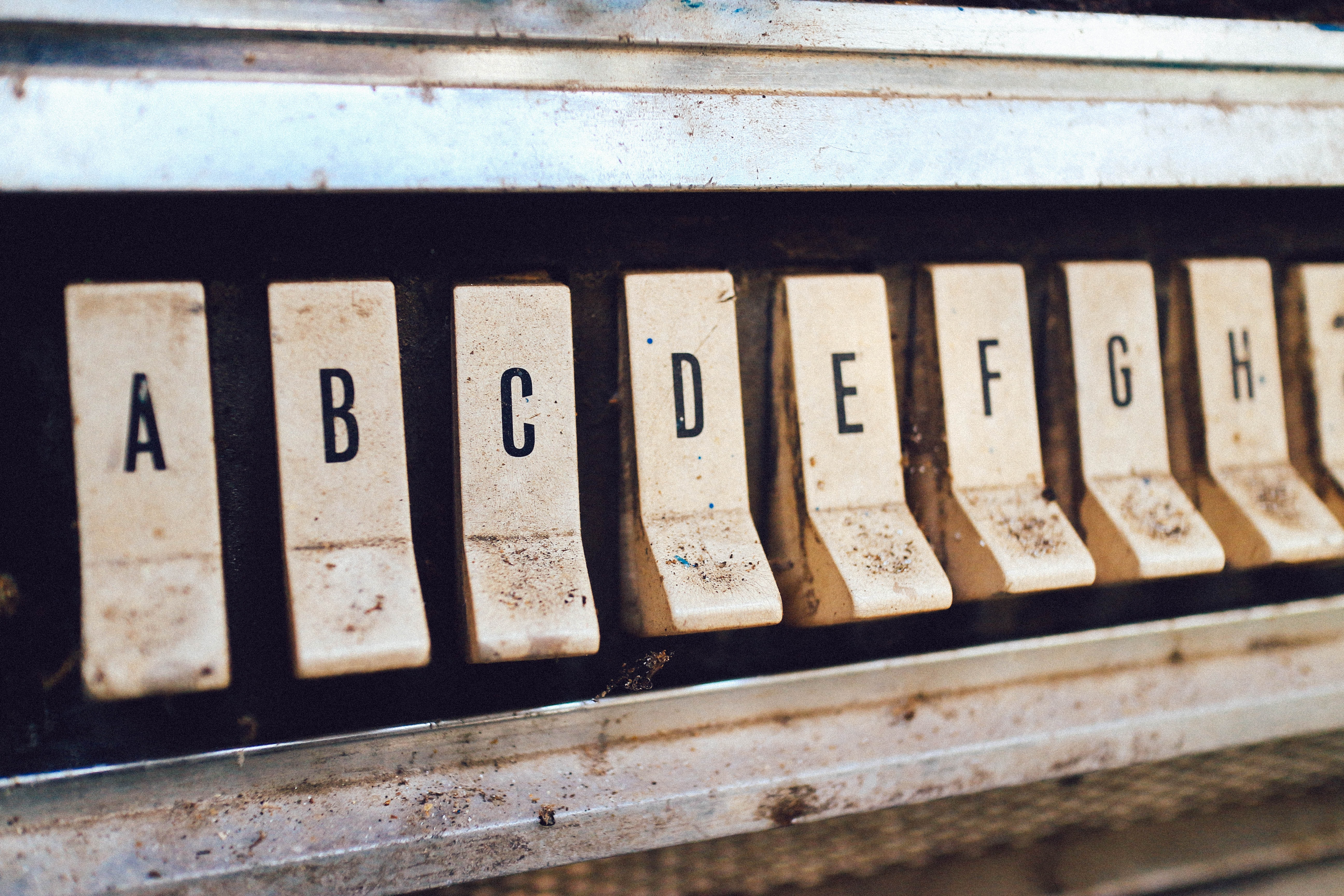 Letter buttons on an old, dirty jukebox.