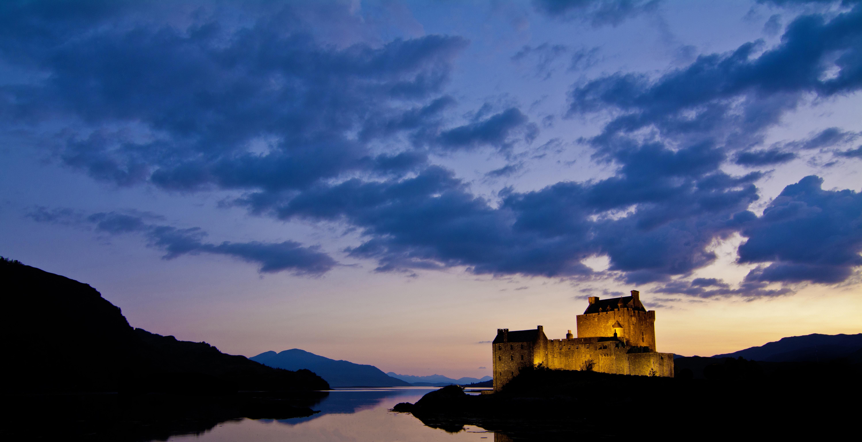 A lit up castle near a lake on an evening