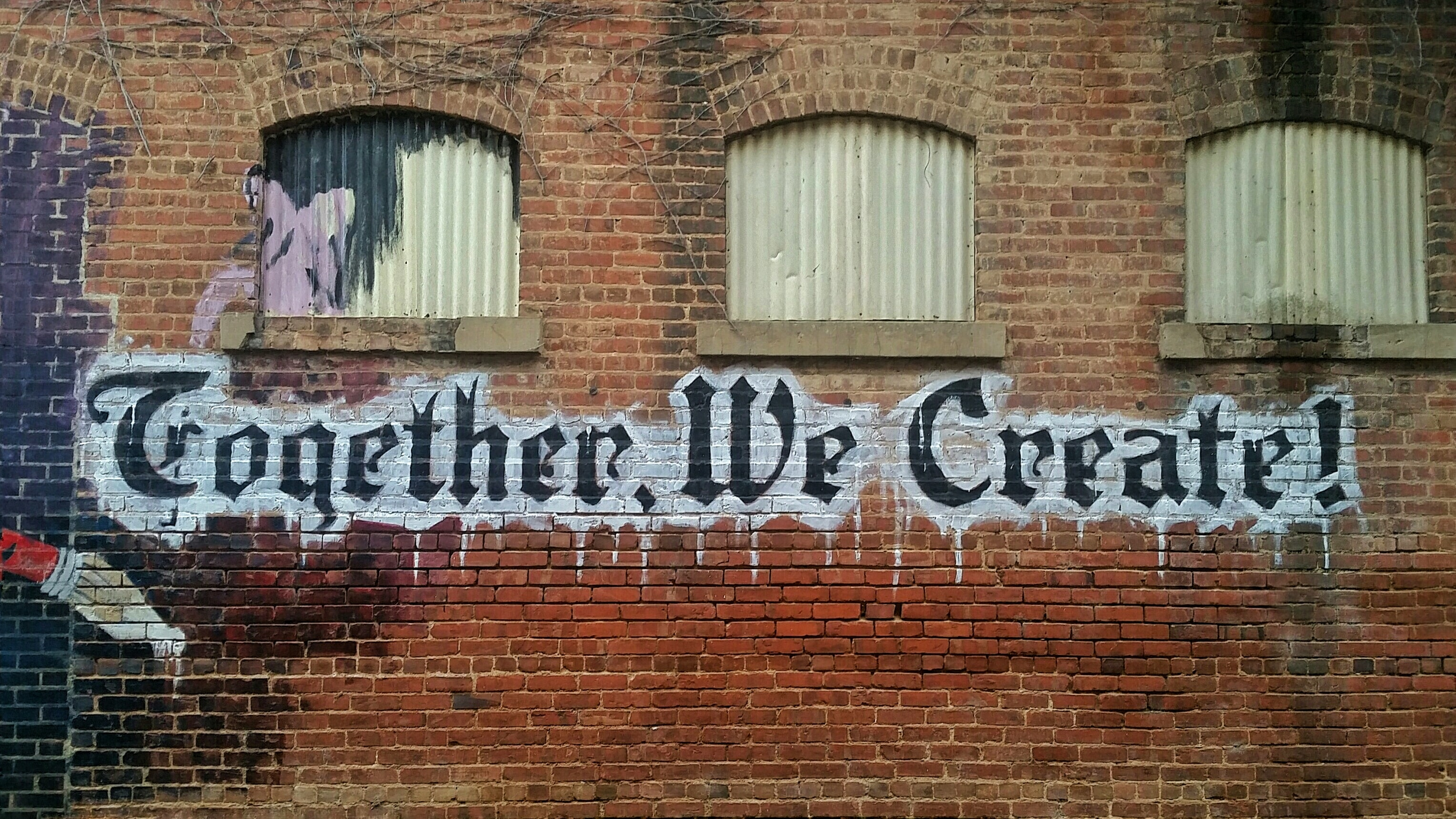 "Graffiti words read ""Together, we create!"" below small windows on a brick wall"