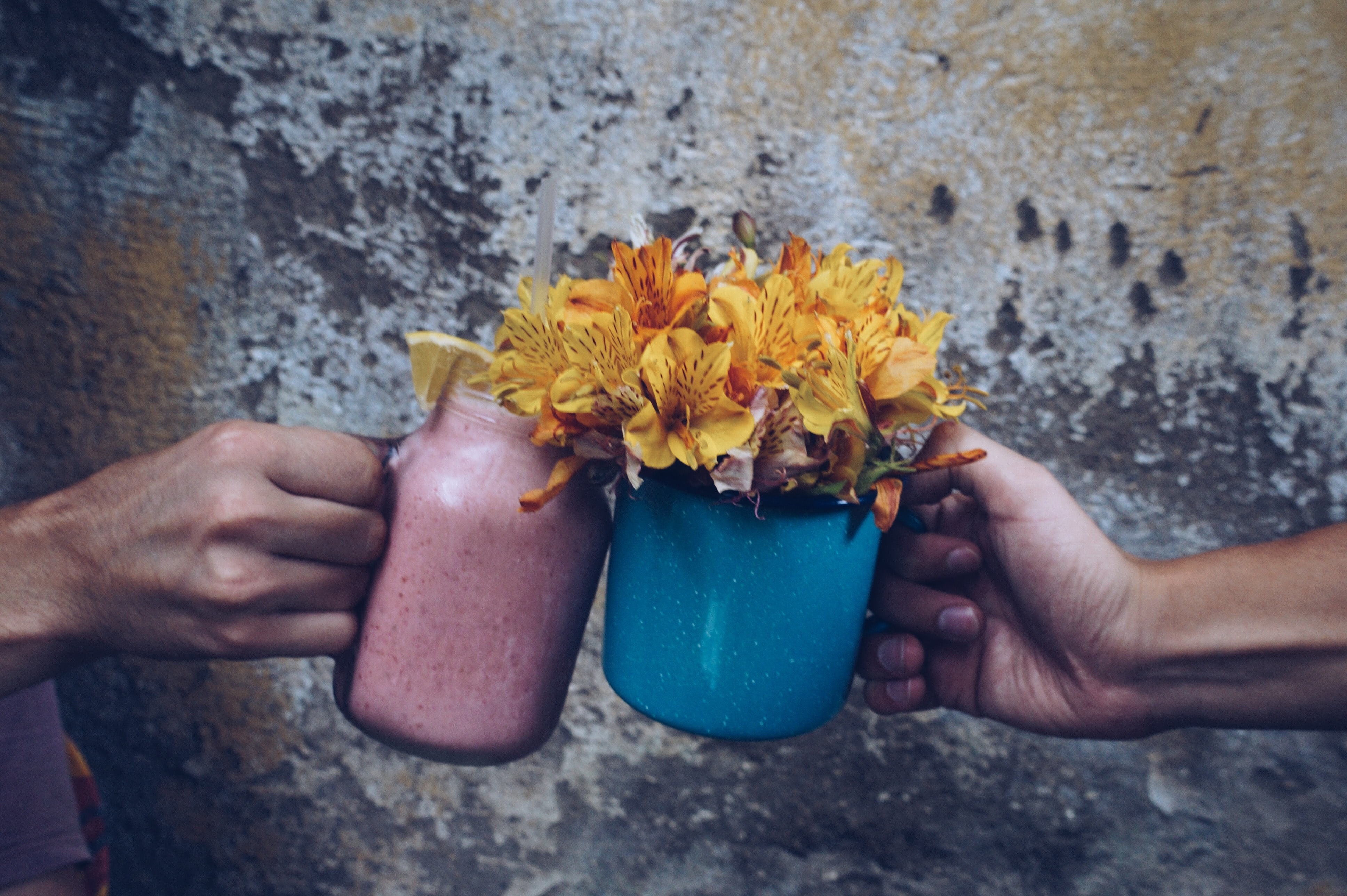 Two people clinking mugs with yellow flowers inside them