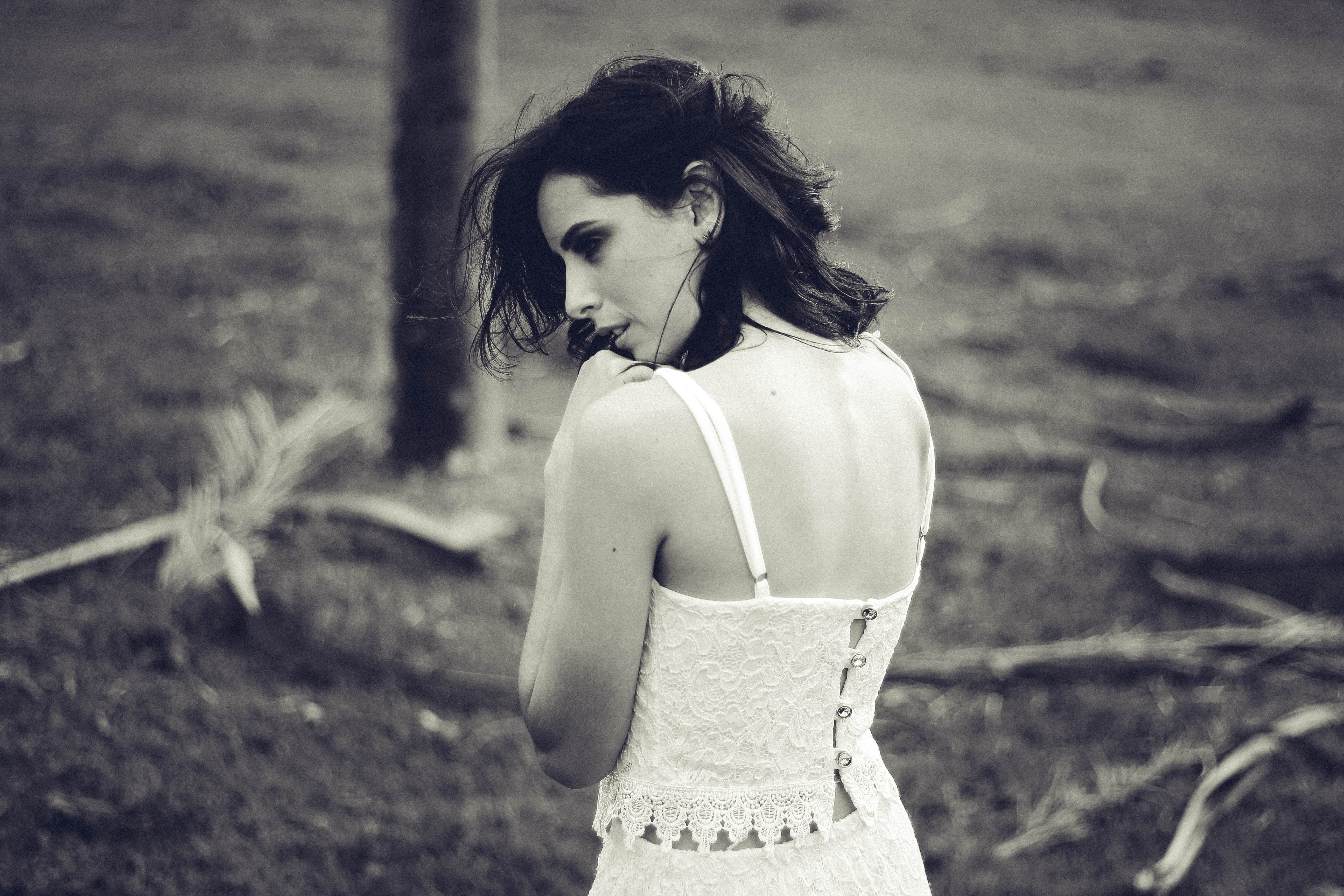 Black and white shot from behind of brunette woman in lace dress standing