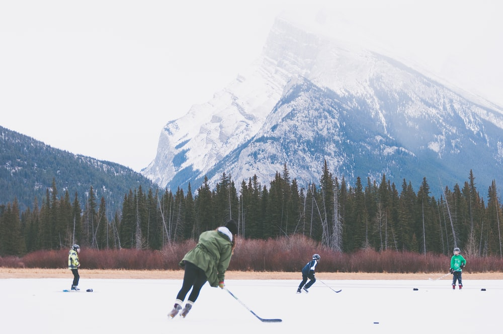 people playing hockey on icefield at datyime