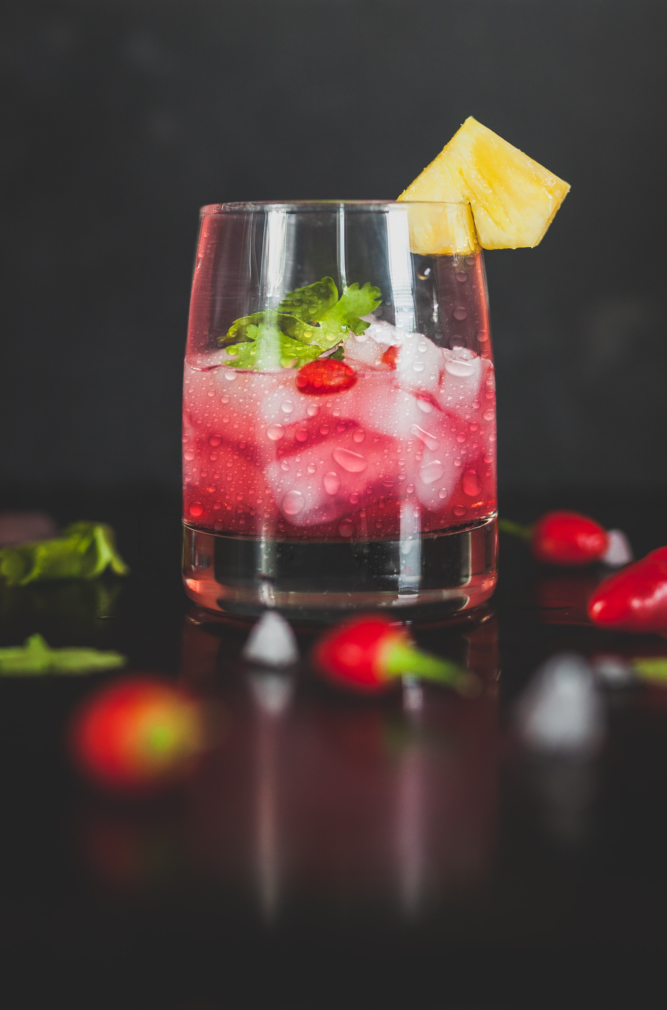 Macro view of cocktail drink in a glass with ice garnished with pepper, leaf and fruits