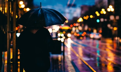 person walking on street while holding black umbrella near cars on road at nighttime night teams background