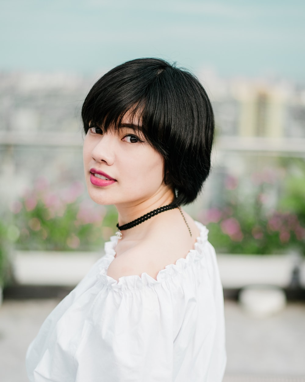 selective focus photo of woman wearing white top and black choker necklace