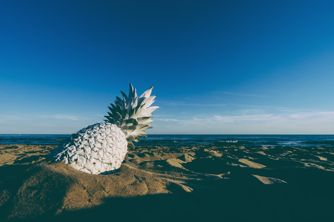 white pineapple on the beach at sunset