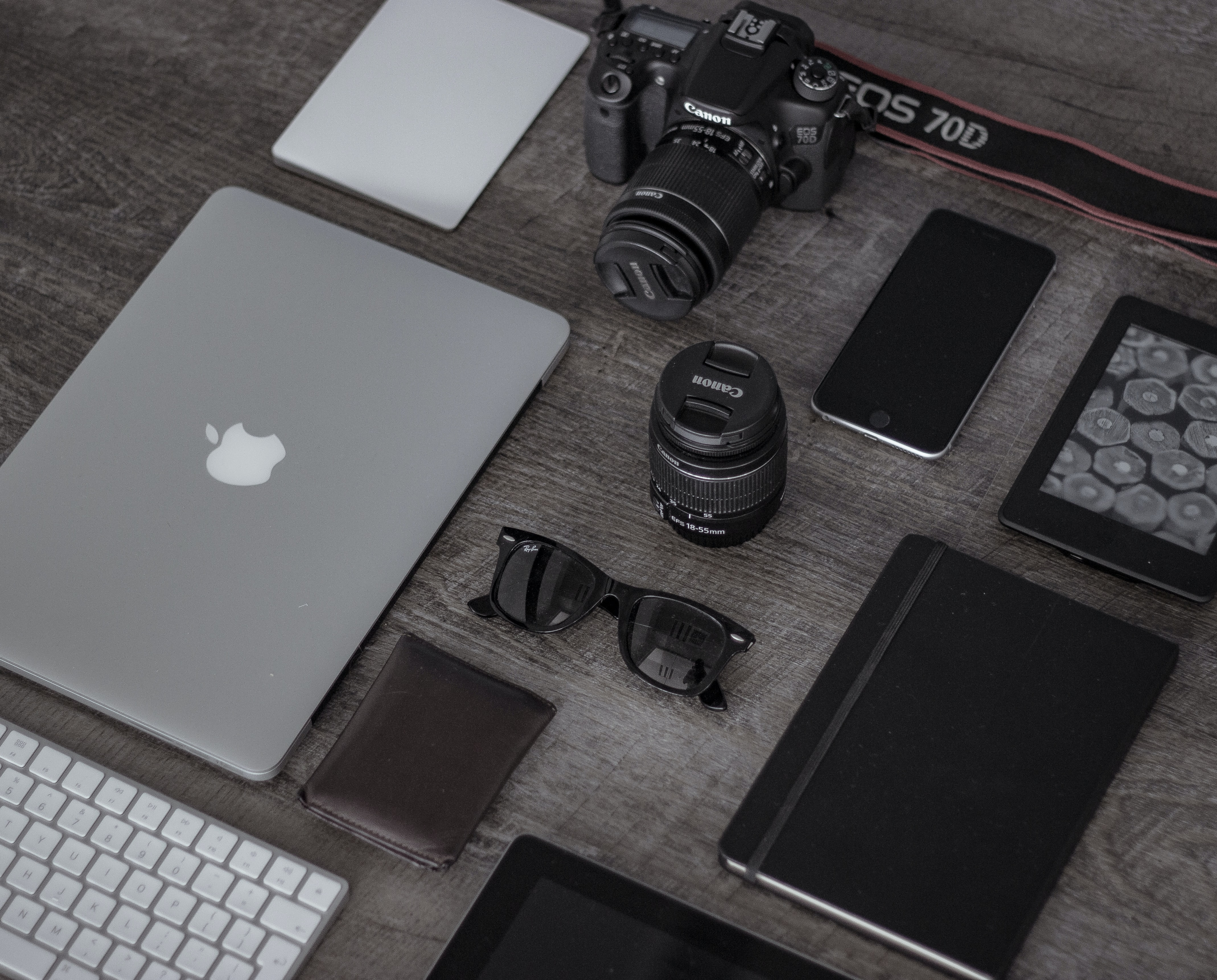 A flatlay with a long-lens camera, a MacBook, an iPhone, a Kindle and a notebook