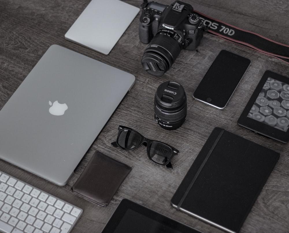 iPad near sunglasses, wallet, and DSLR camera