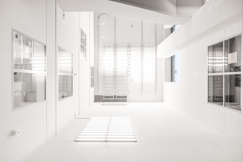 A white industrial interior with windows and fixtures on the walls