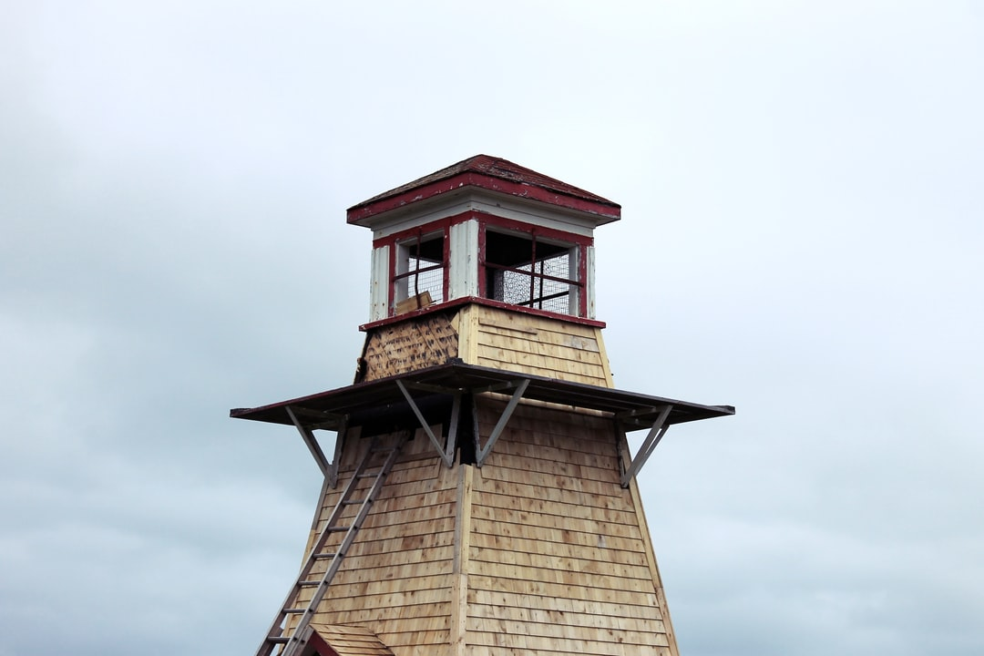 A shingled lighthouse with a red roof set against a cloudy, open sky.