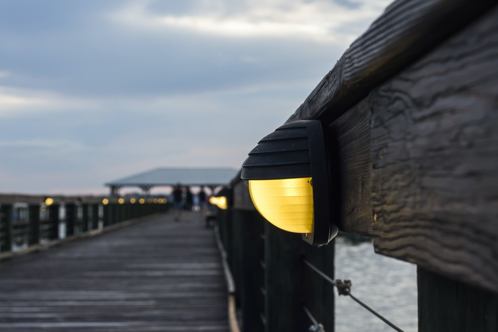 wooden dock with lights turned on at night