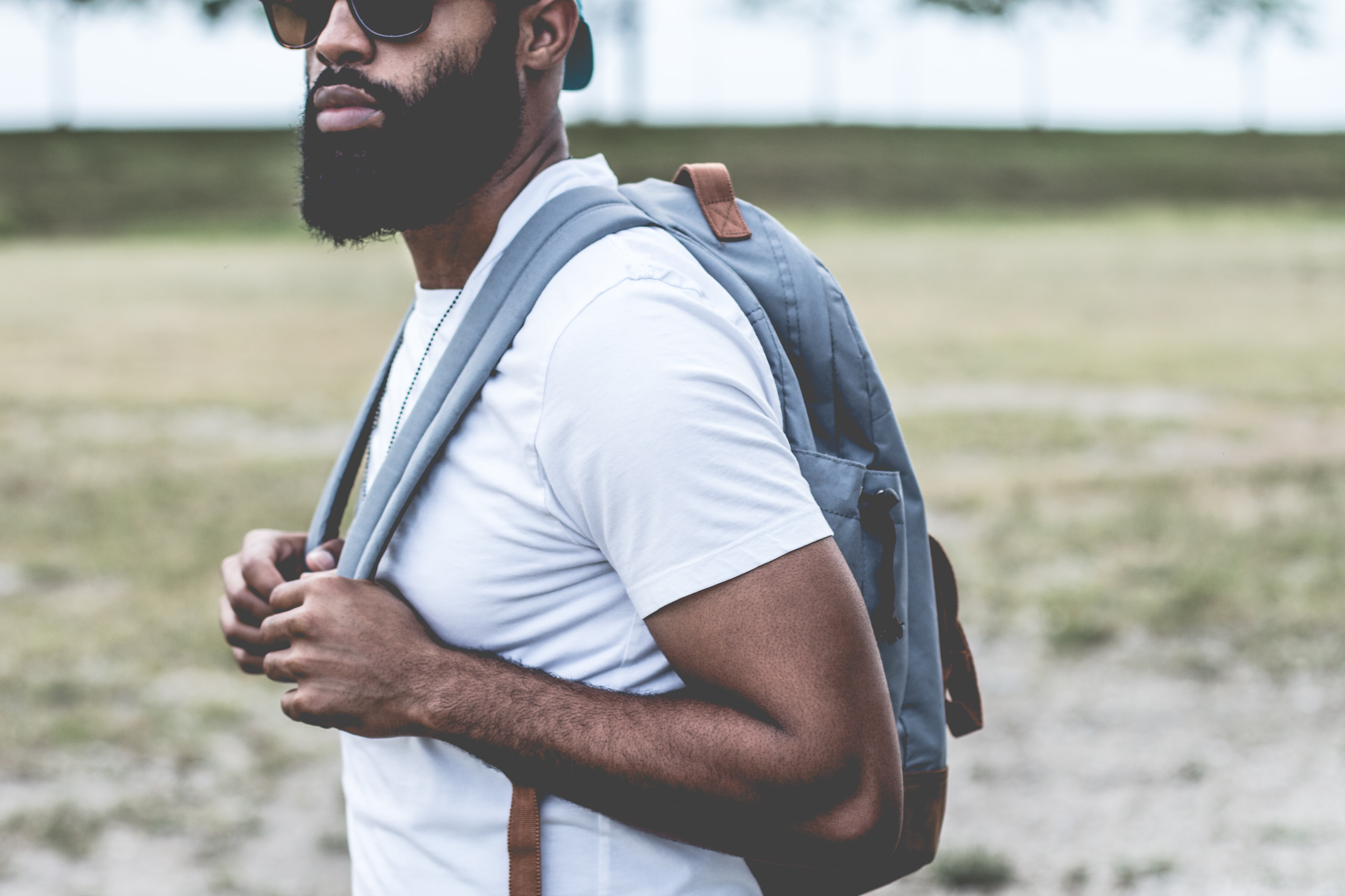 Man with a beard and sunglasses wearing a backpack outside