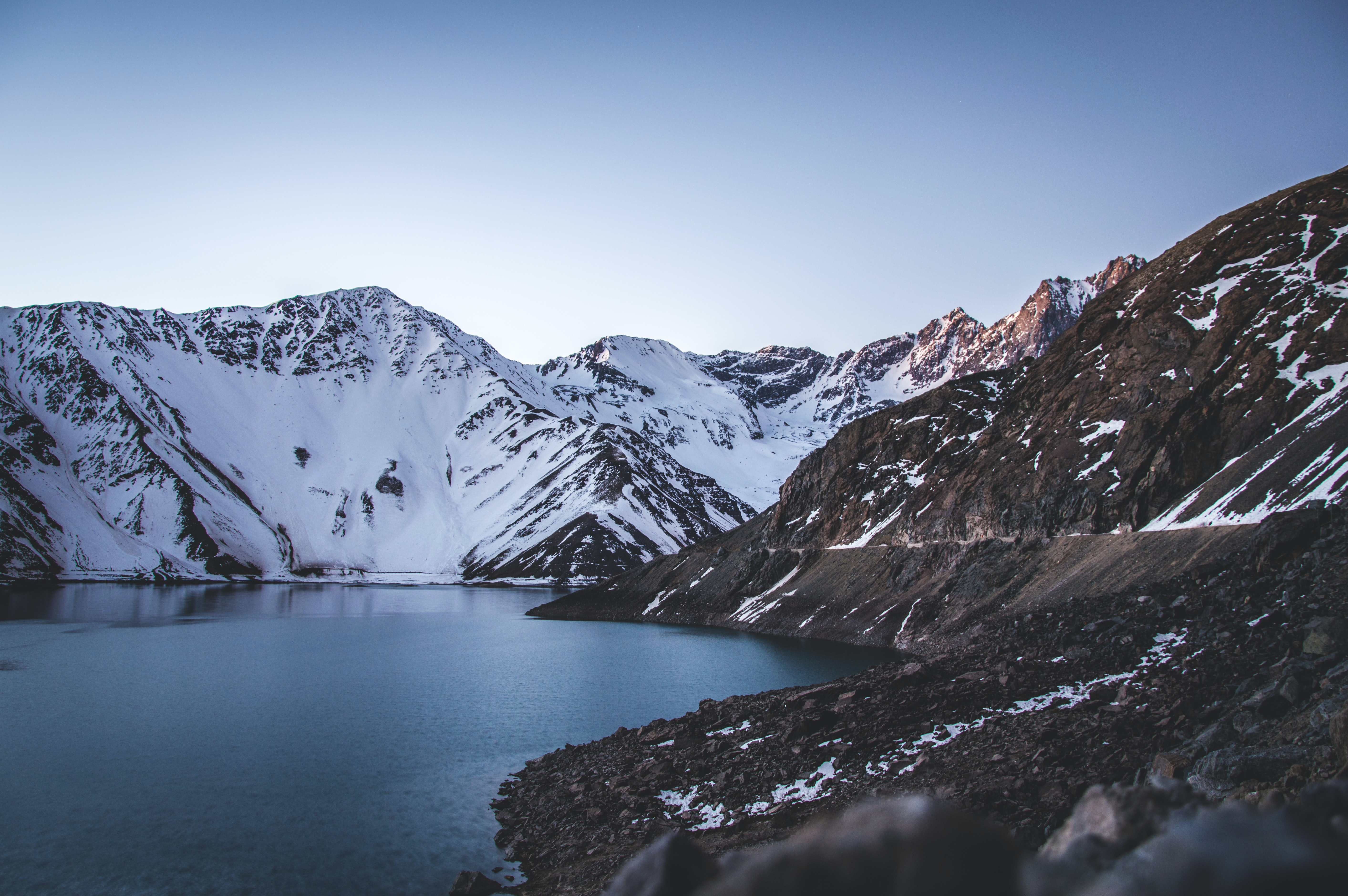 Snow covered mountains surround a blue lake in El Yeso Dam.