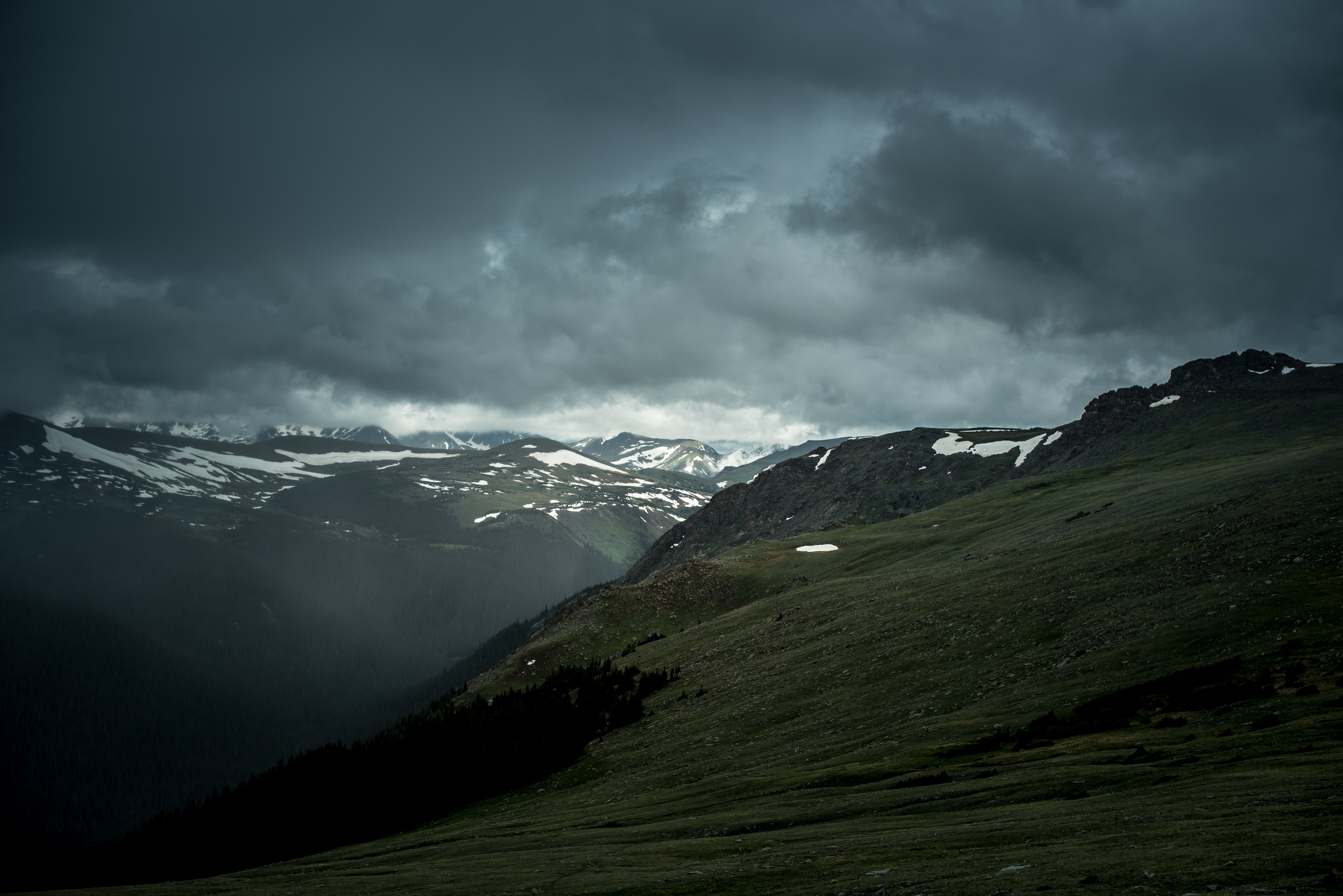 Mountains covered by grass and snow with deep hanging clouds in the sky