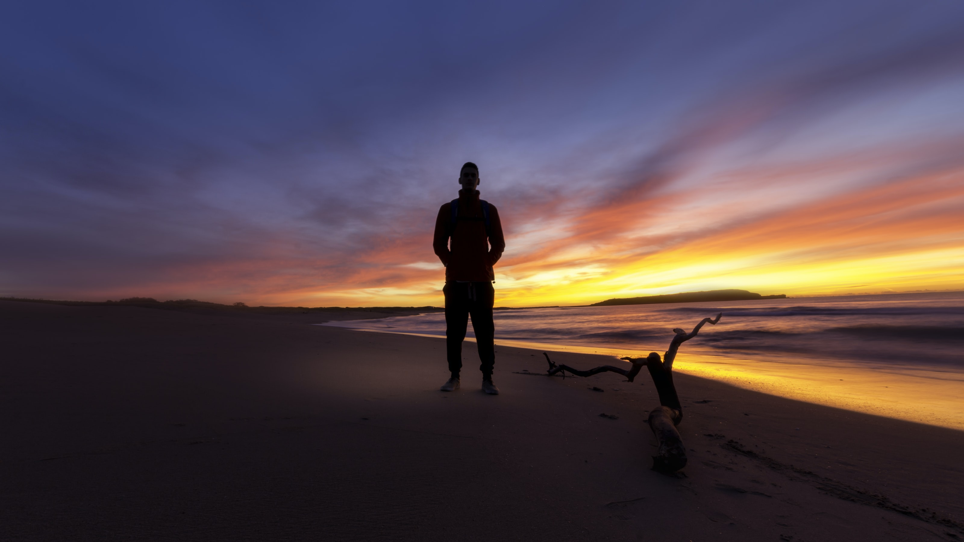 A male silhouette on a Sydney beach during the late evening with a strong sun in the background
