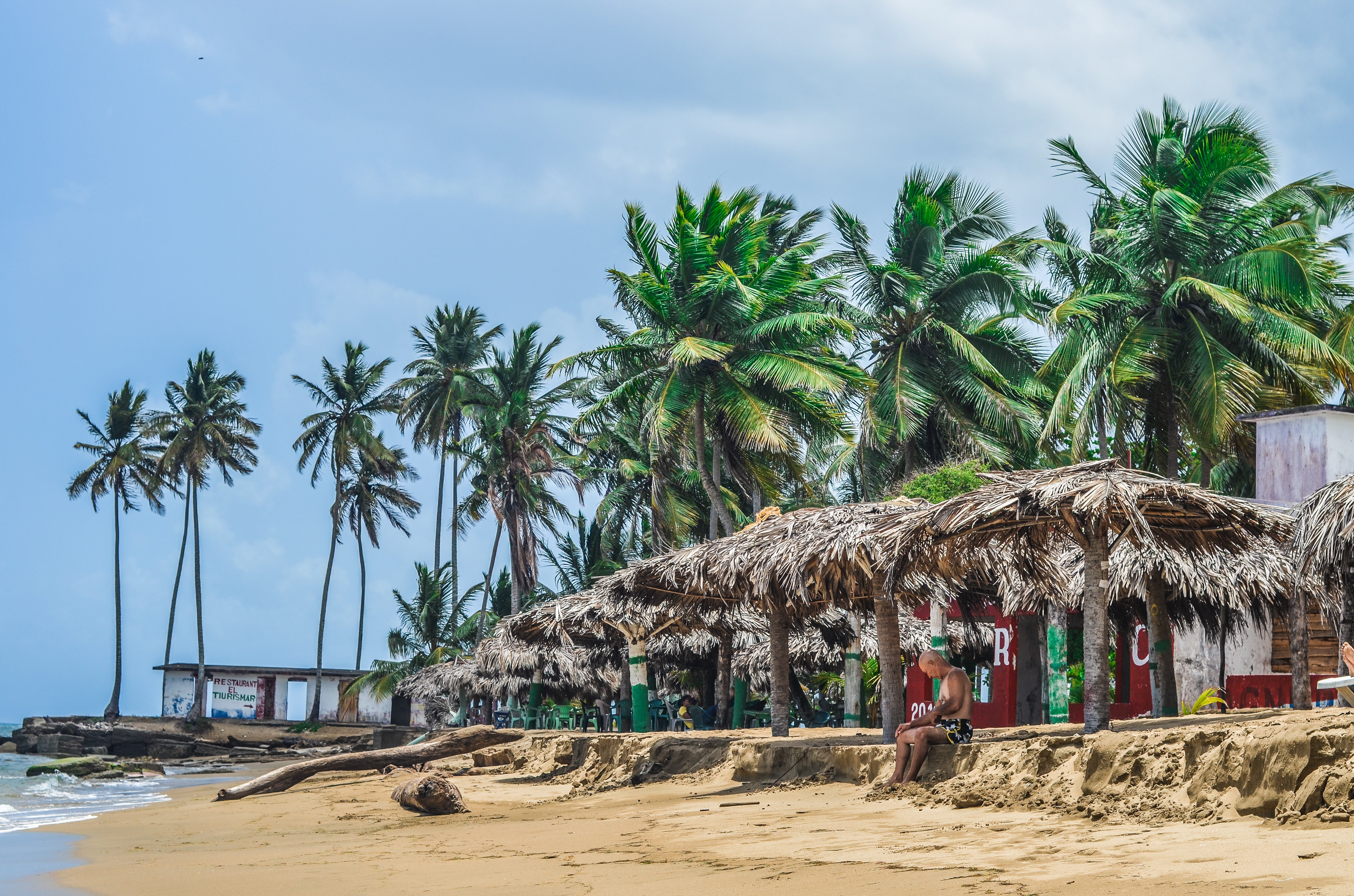 A lone man sitting on the beach under a thatched roof